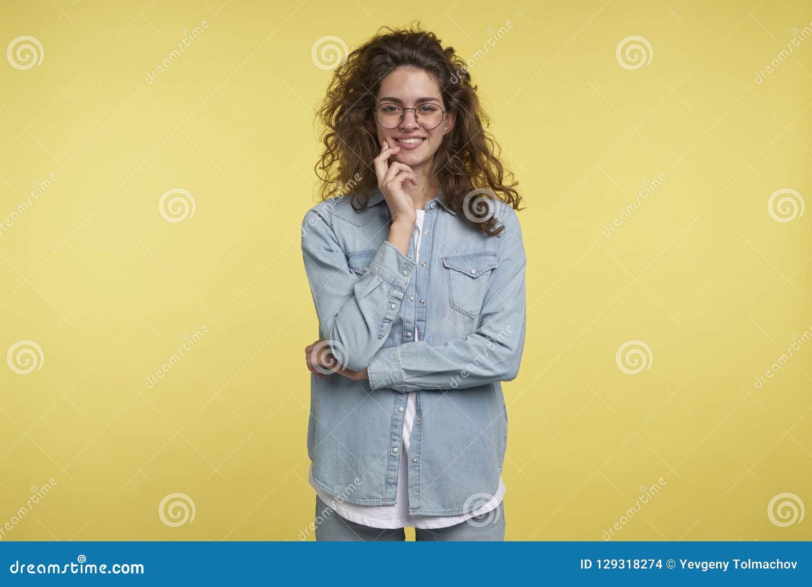 Bella femmina castana con capelli ricci, ridenti e tenenti mano al suo fronte mentre stando isolato, giallo
