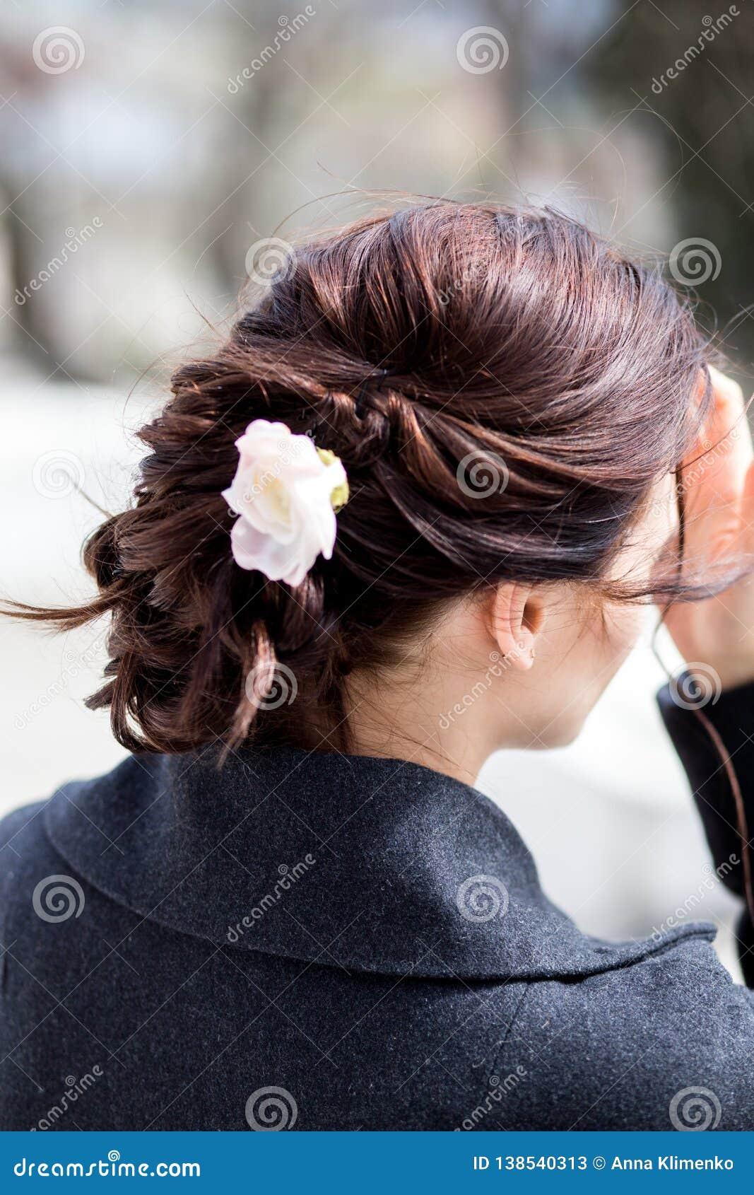 Bella giovane bruna con la pettinatura creativa dell intrecciatura con un fiore