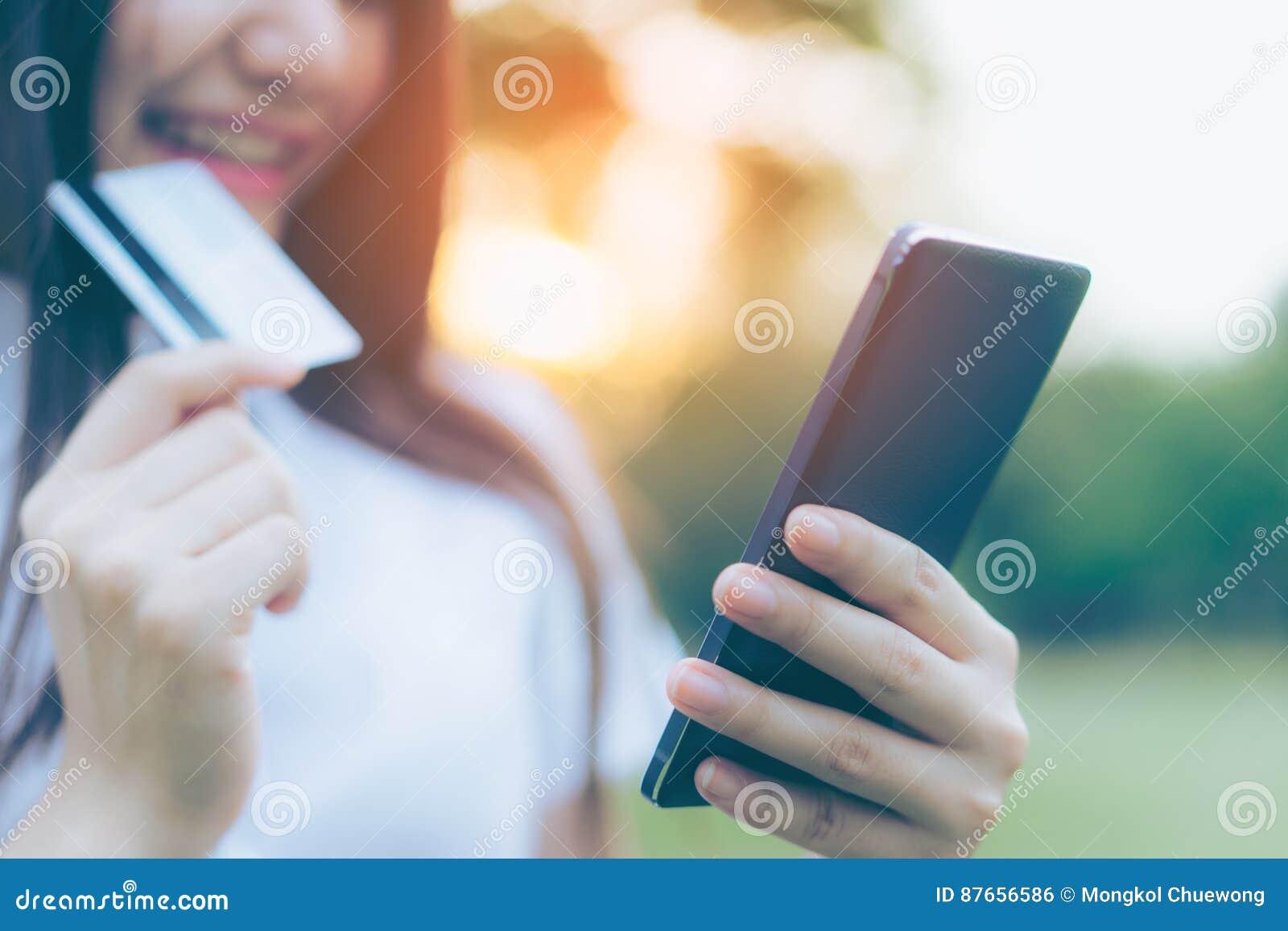 Bella giovane donna asiatica che per mezzo del suo smartphone per comperare online