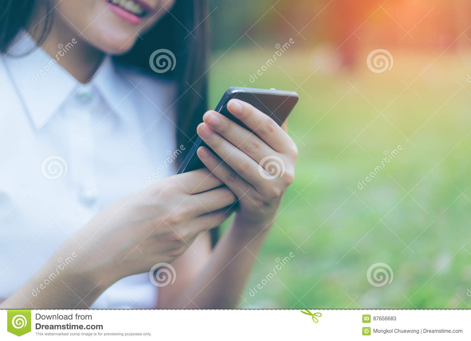 Bella giovane donna asiatica che sorride mentre leggendo il suo smartphone