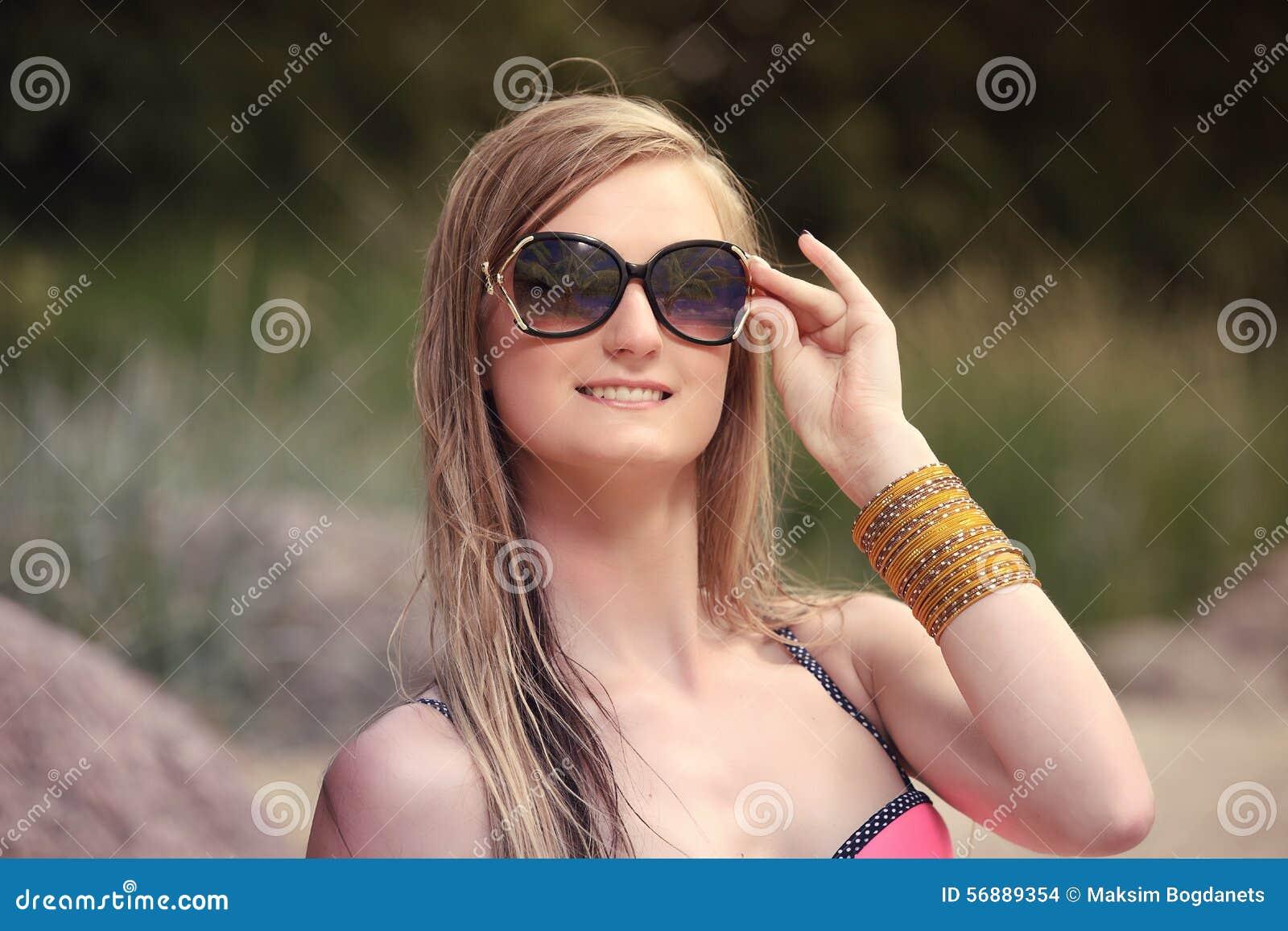 Bella giovane donna in bikini sulla spiaggia soleggiata