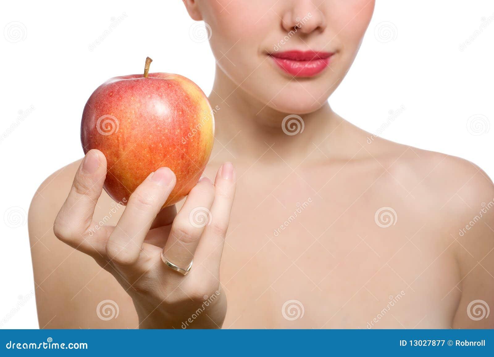 Bella giovane donna bionda che offre mela rossa