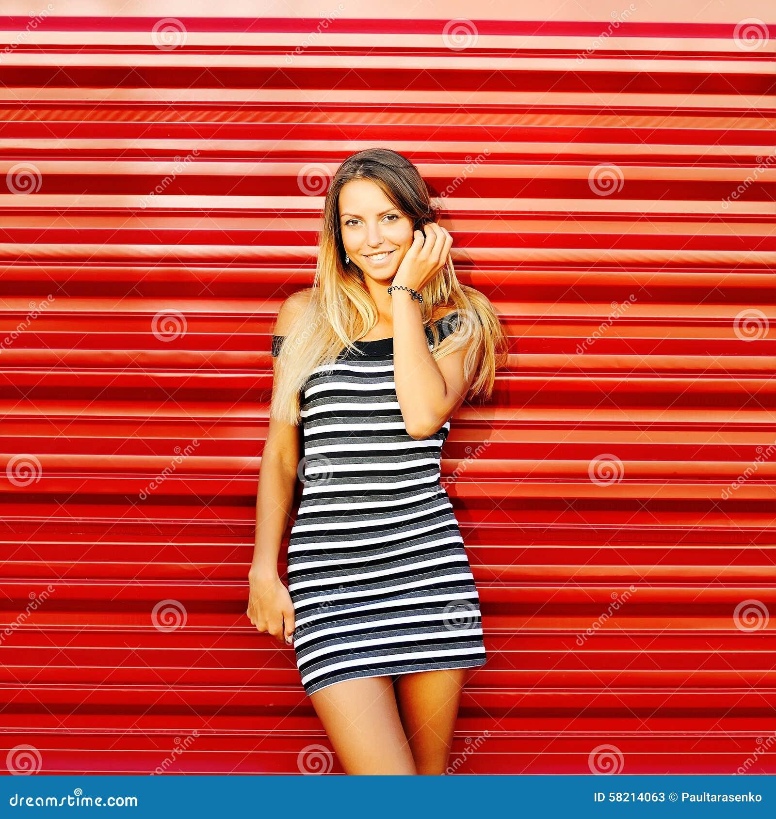 Bella giovane donna bionda sexy che posa dietro una parete rossa - poliziotto