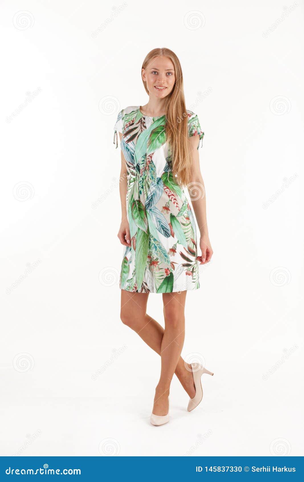 Bella giovane donna bionda in vestito bianco con la stampa tropicale isolata su fondo bianco