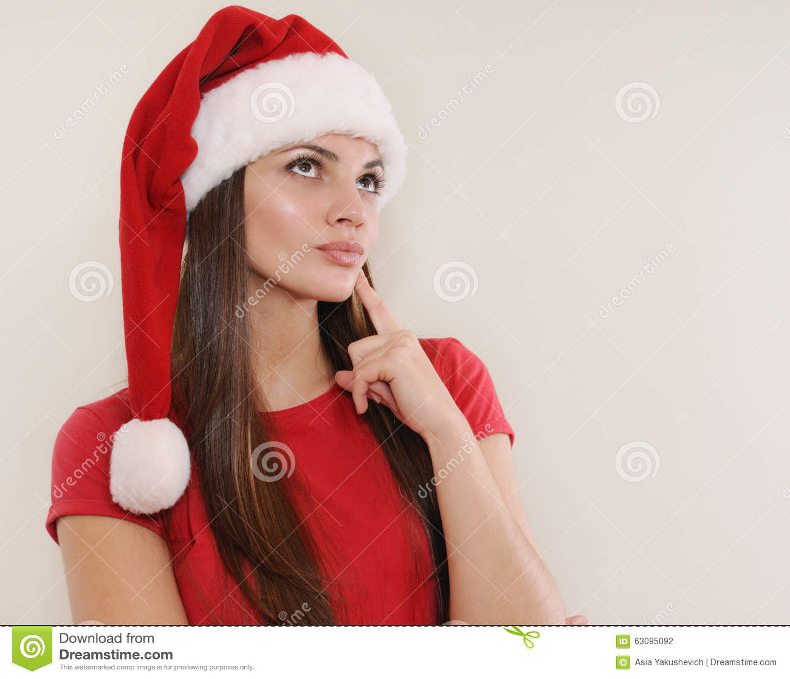 Bella giovane donna in cappello di Santa che pensa al regalo di Natale