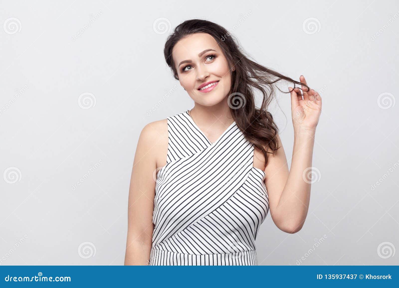 Bella giovane donna castana ottimista felice con trucco e la condizione a strisce del vestito che toccano capelli, sogno e distog