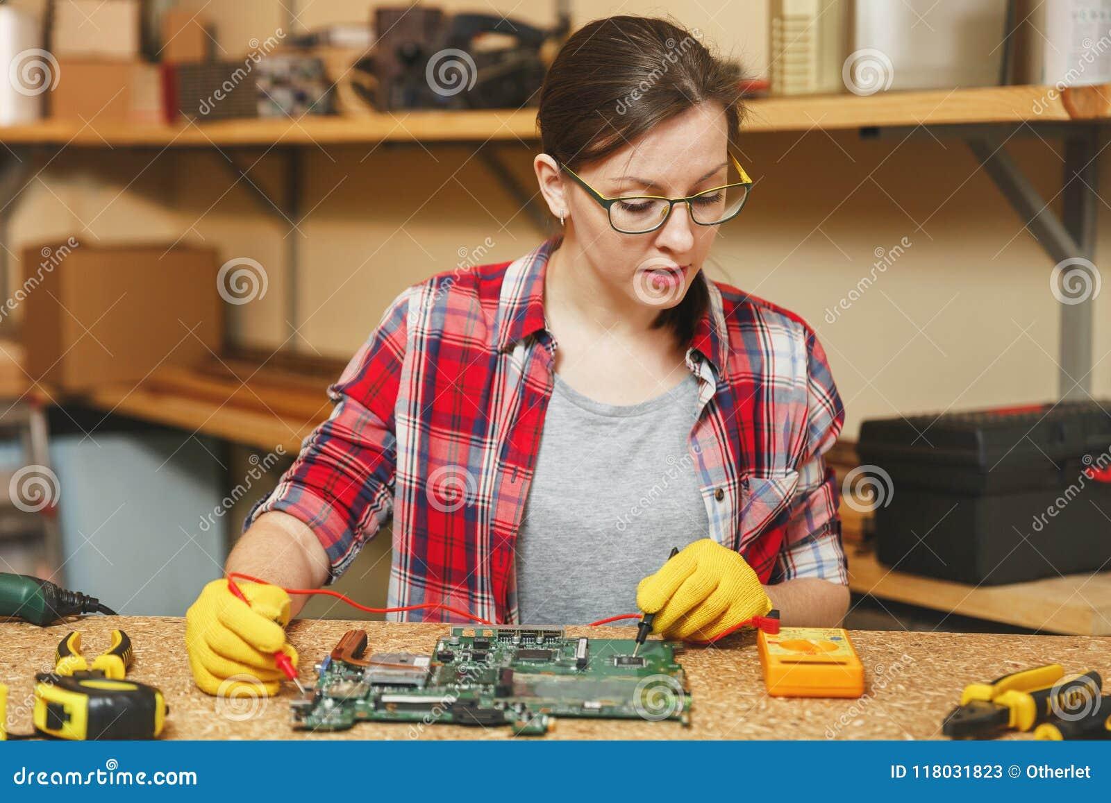 Bella giovane donna caucasica dei Brown-capelli che lavora nell officina di carpenteria al posto della tavola