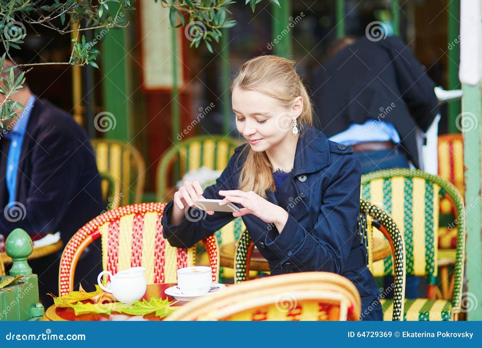 Bella giovane donna che beve in caffè all aperto parigino