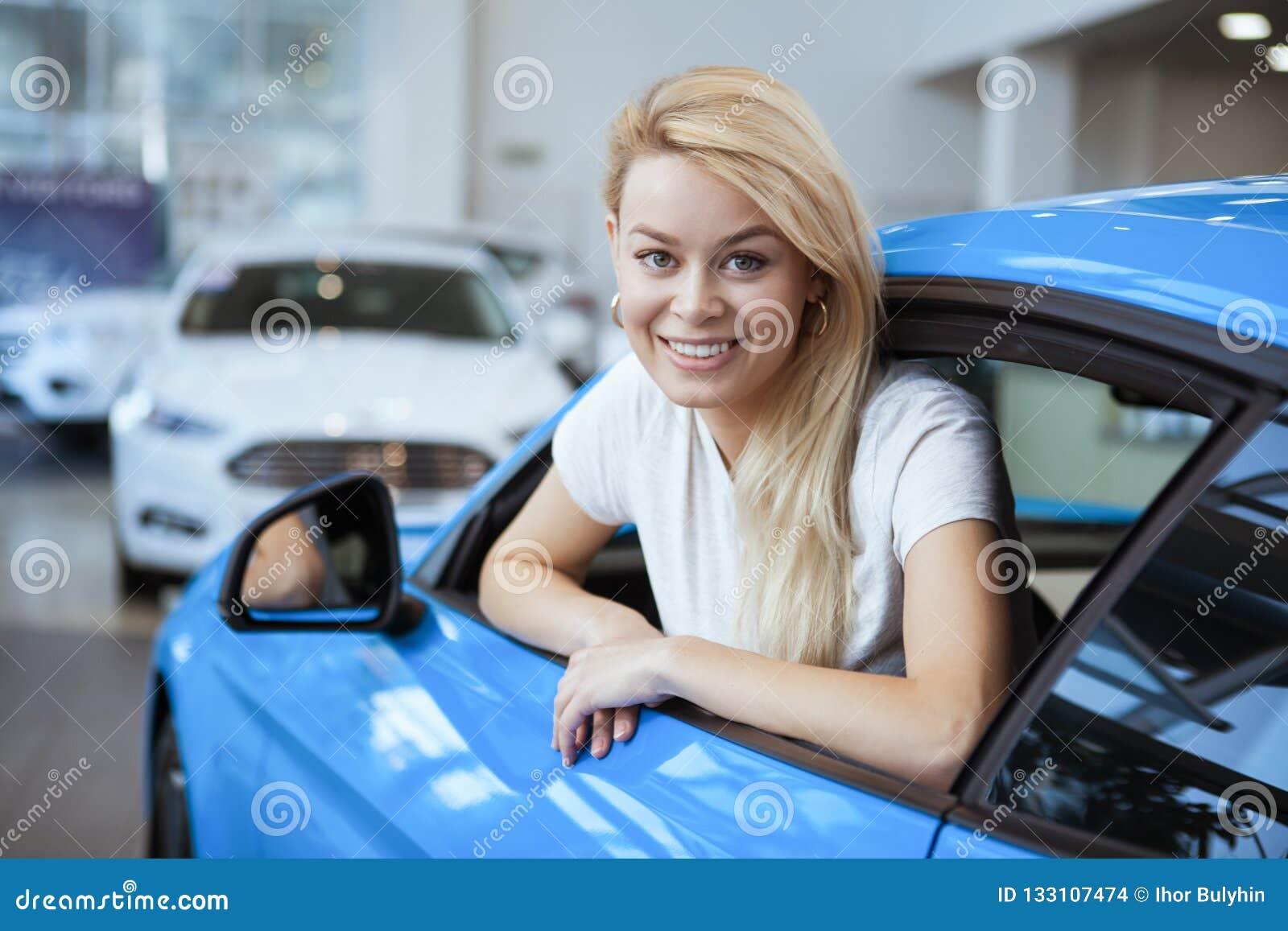 Bella giovane donna che compra nuova automobile alla gestione commerciale