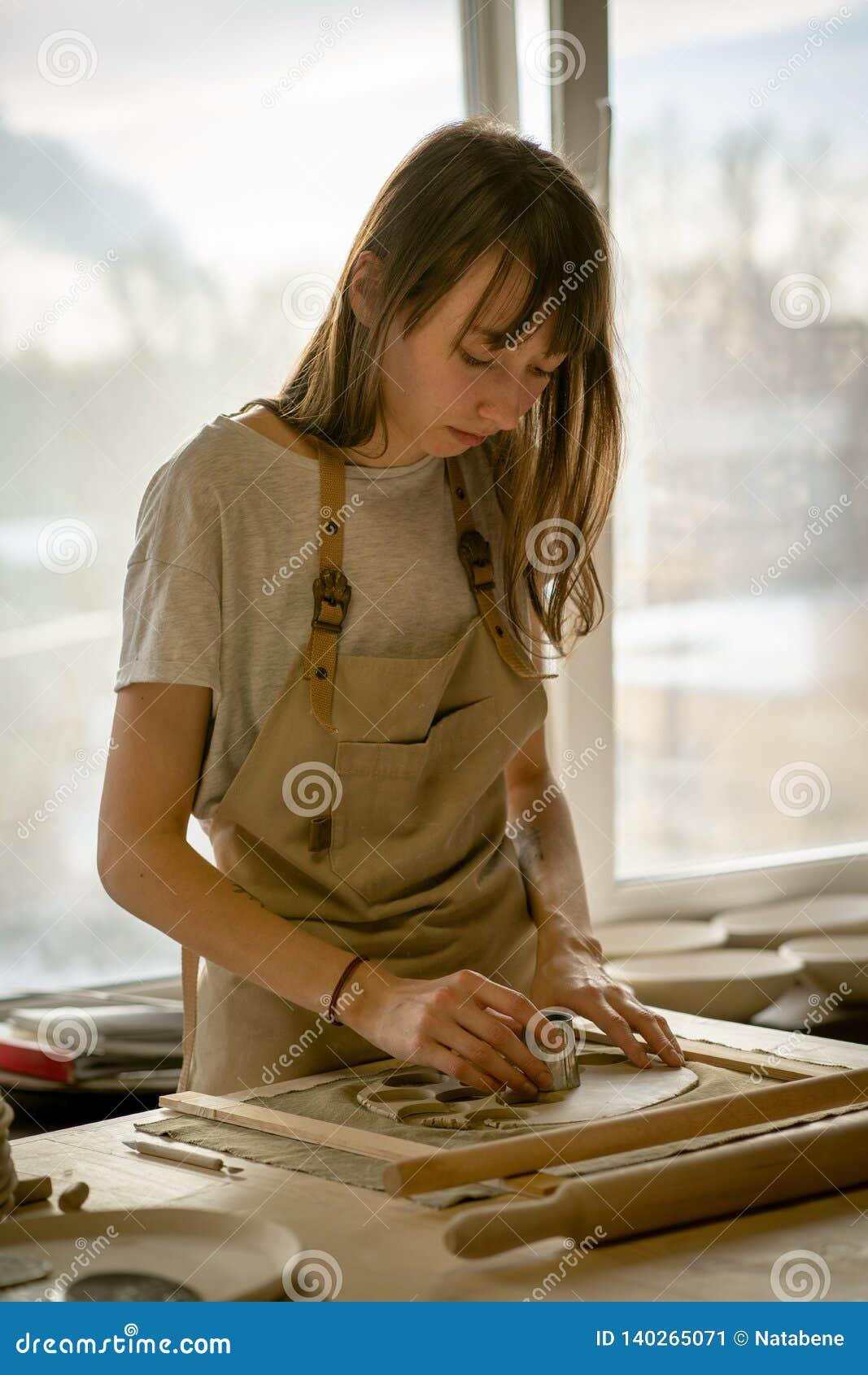 Bella giovane donna che fa gli articoli ceramici, modellanti una forma in posto di lavoro alla luce del sole Concetto per la donn