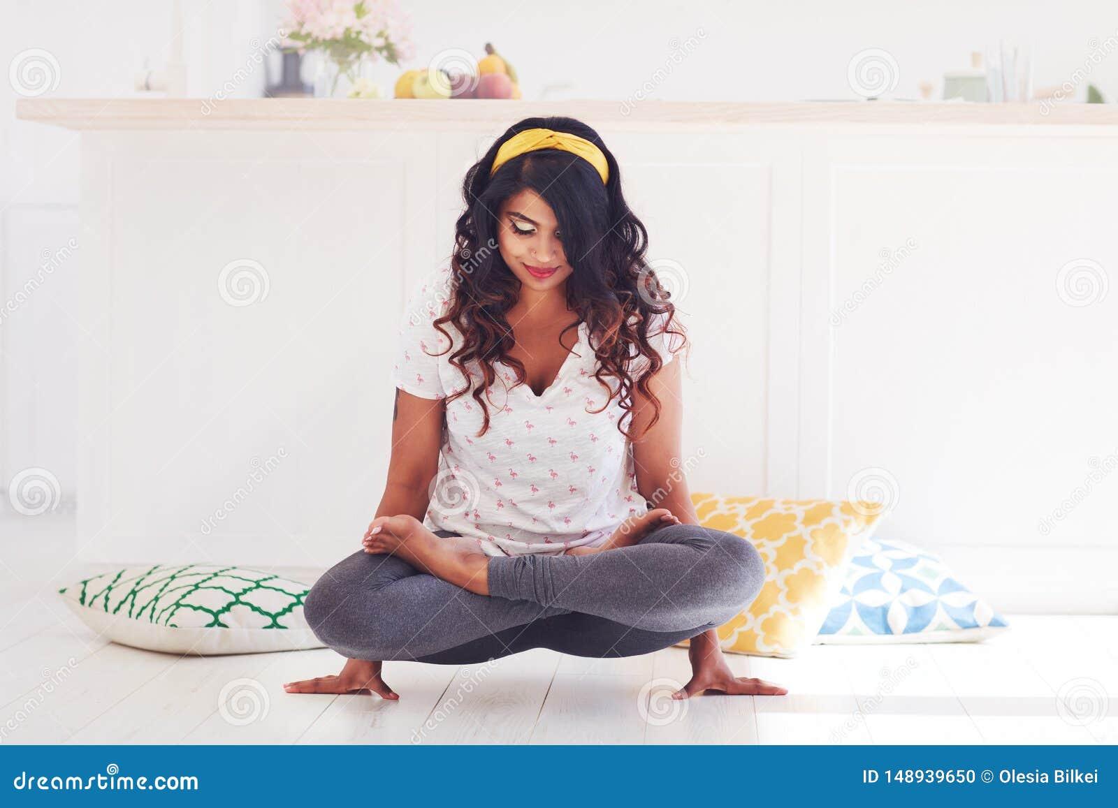 Bella giovane donna che fa posa del galletto di yoga di Kukkutasana a casa