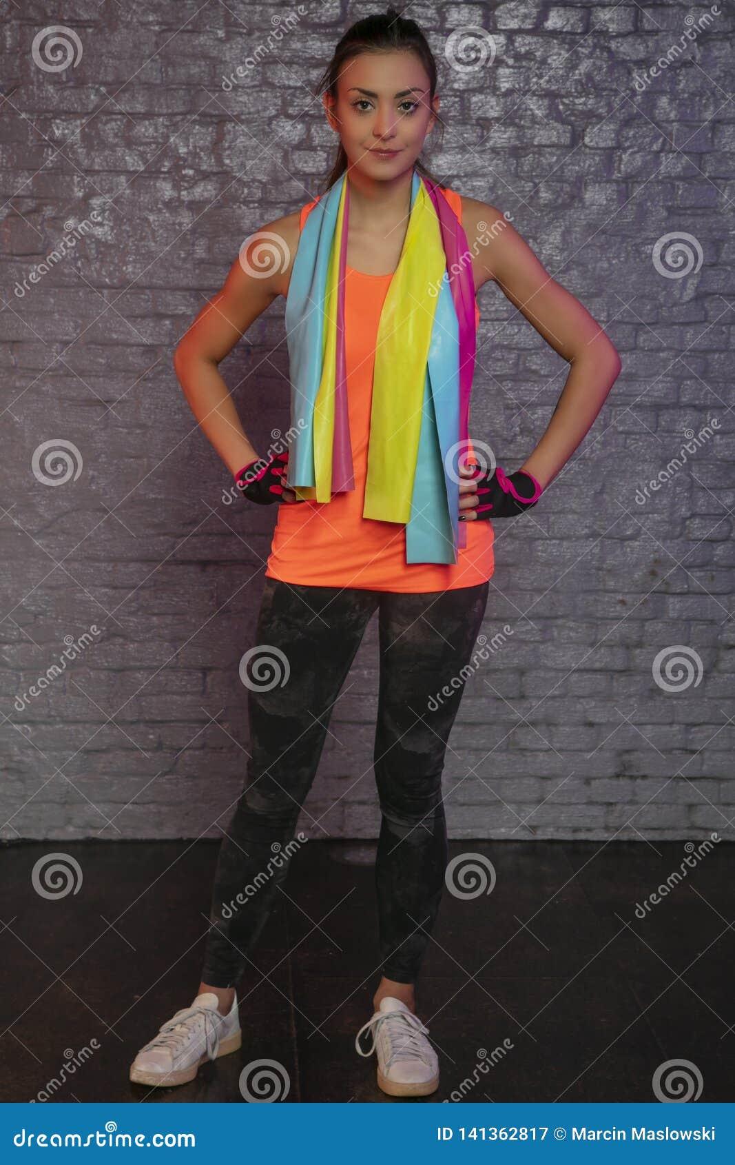 Bella giovane donna che pratica con le bande elastiche