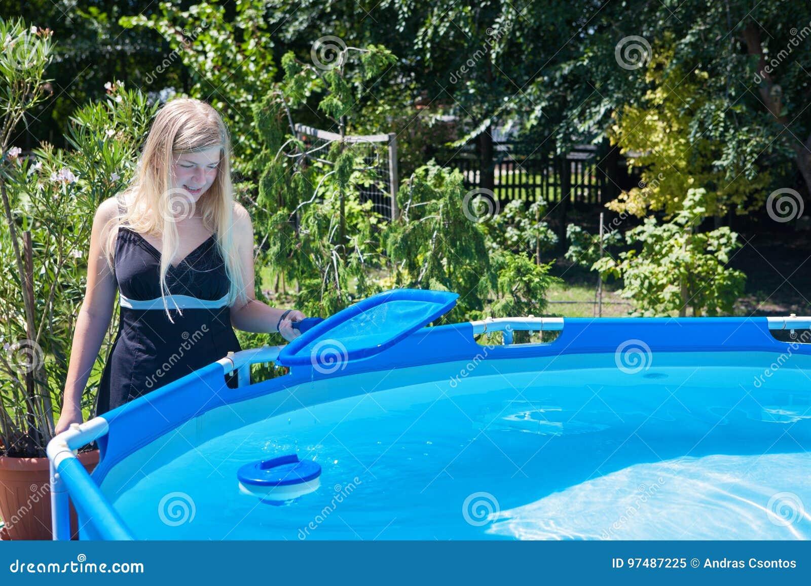 Bella giovane donna che pulisce una piscina piegante con la SK