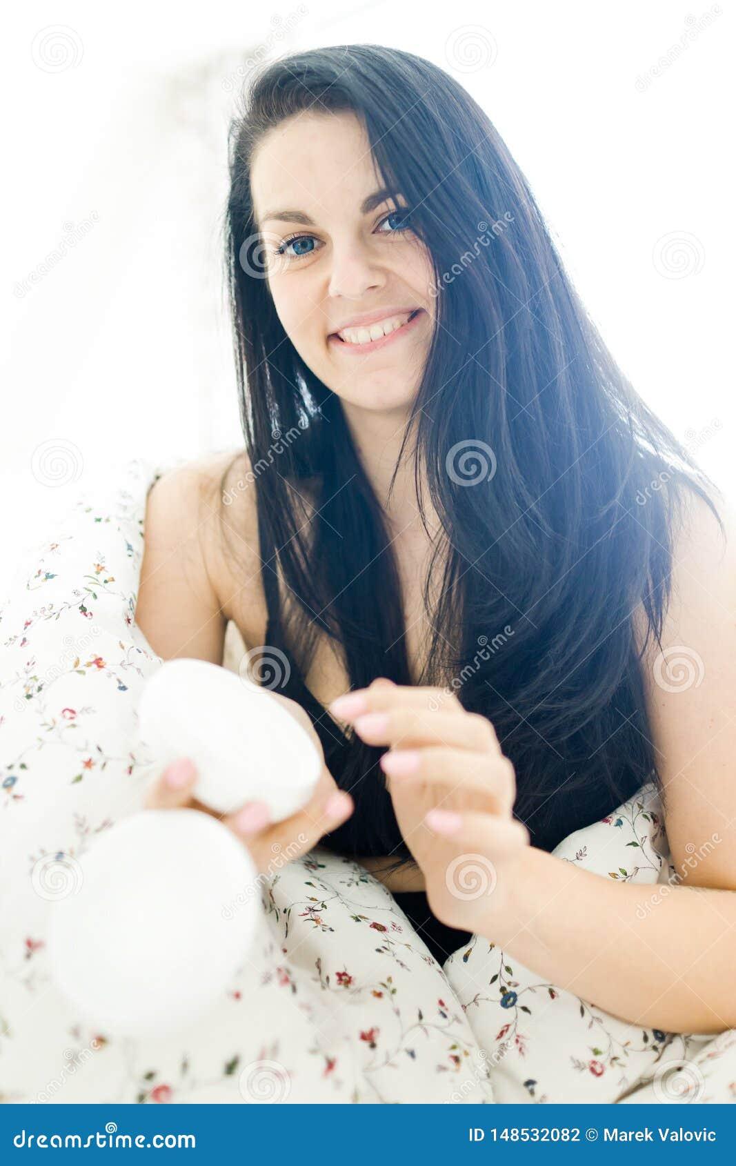 Bella giovane donna che si preoccupa per la sua pelle con lozione d idratazione