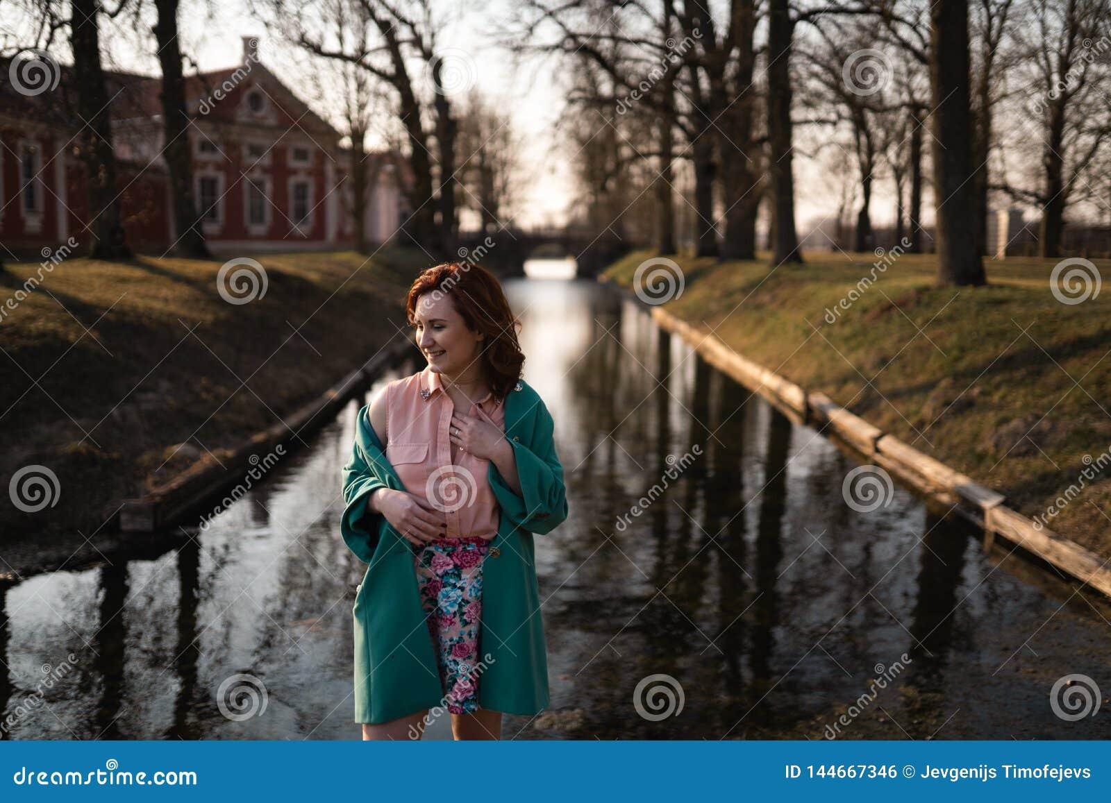 Bella giovane donna che si rilassa vicino ad un fiume del canale in un parco vicino al palazzo in Rundale, Lettonia, 2019