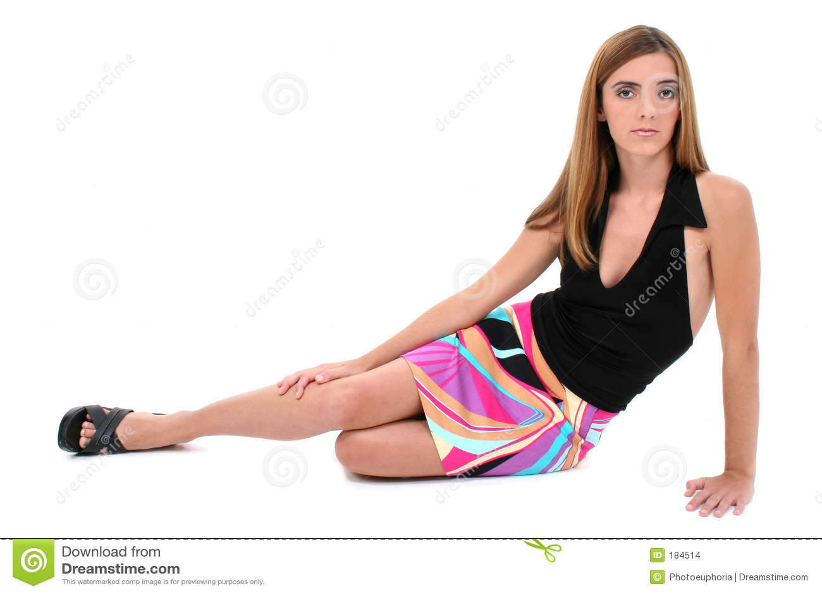 Bella giovane donna che si siede sul pavimento in vestito da estate