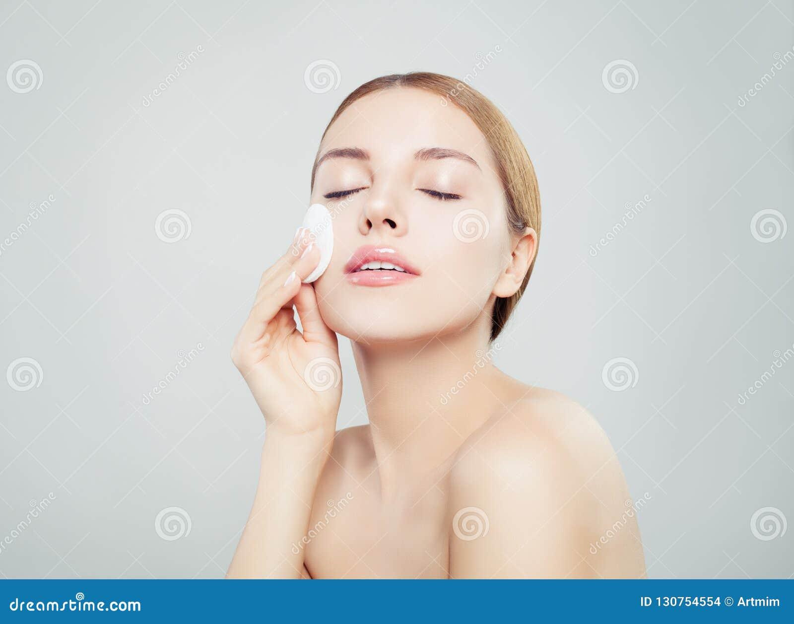 Bella giovane donna con i cuscinetti di cotone puliti Trattamento facciale