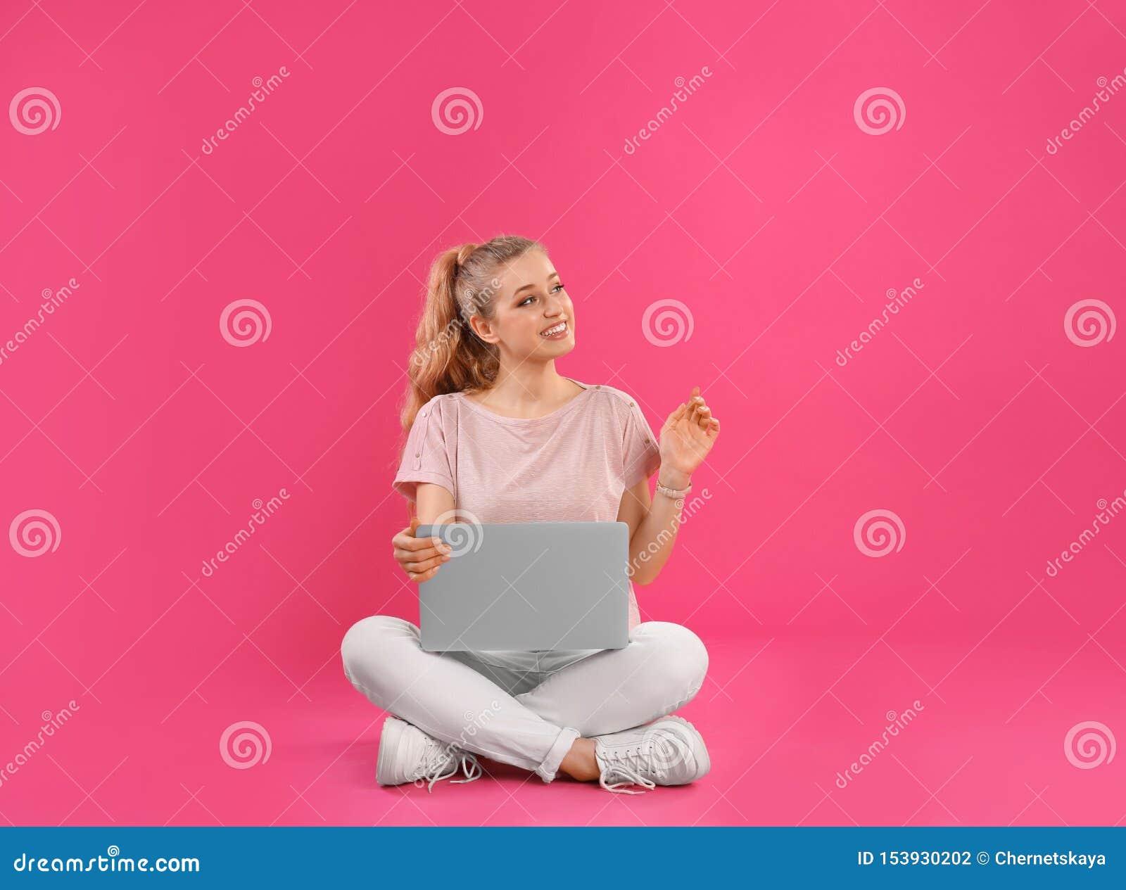 Bella giovane donna con il computer portatile sul rosa