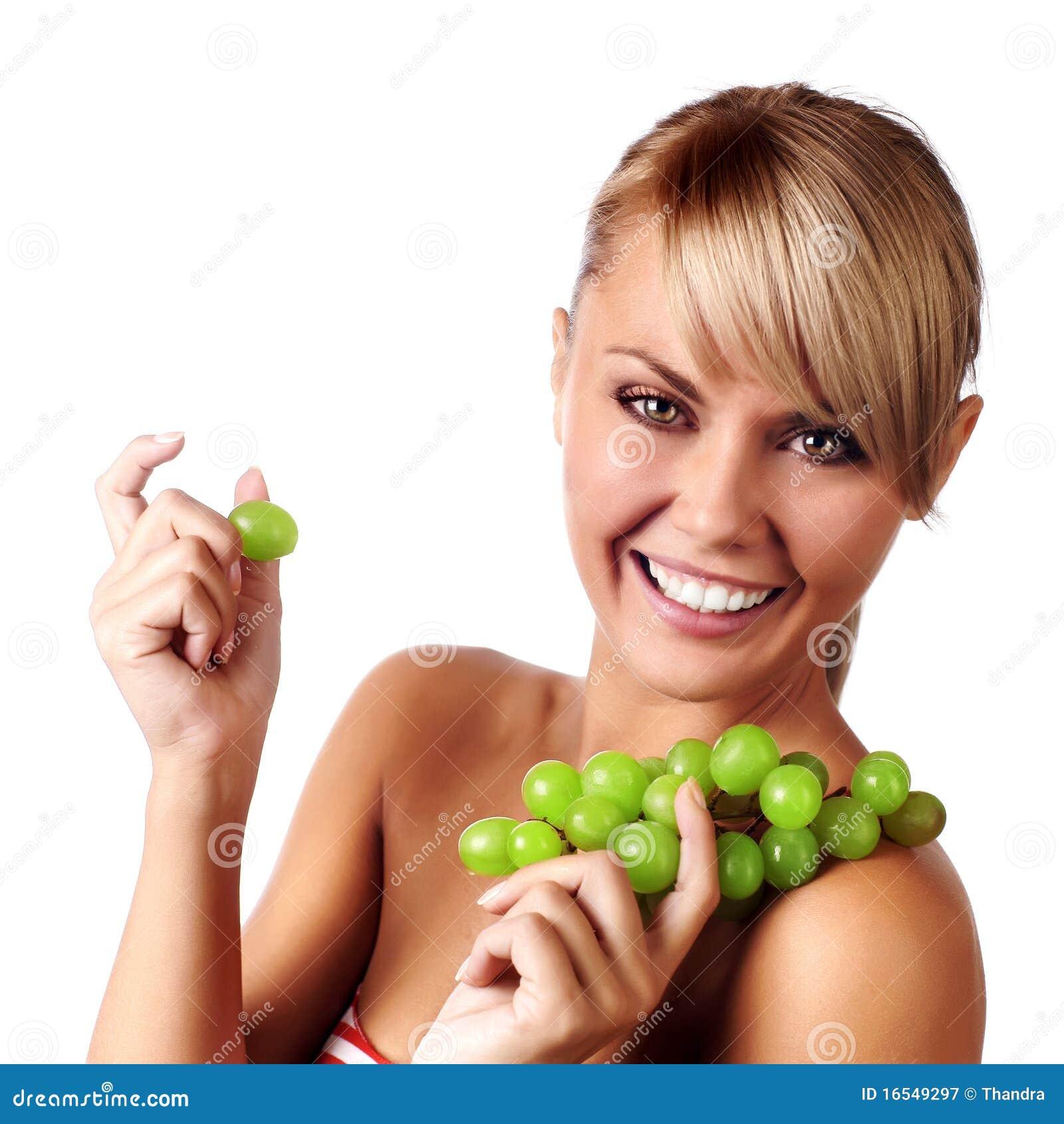Bella giovane donna con il mazzo di uva.