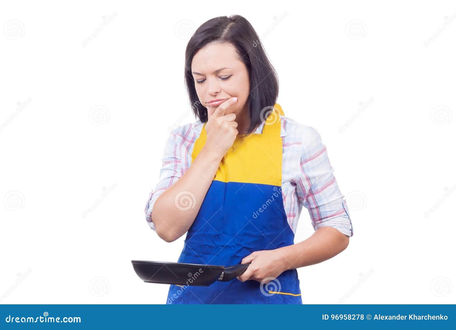 Bella giovane donna con la frittura del Pan Thinking What per preparare f