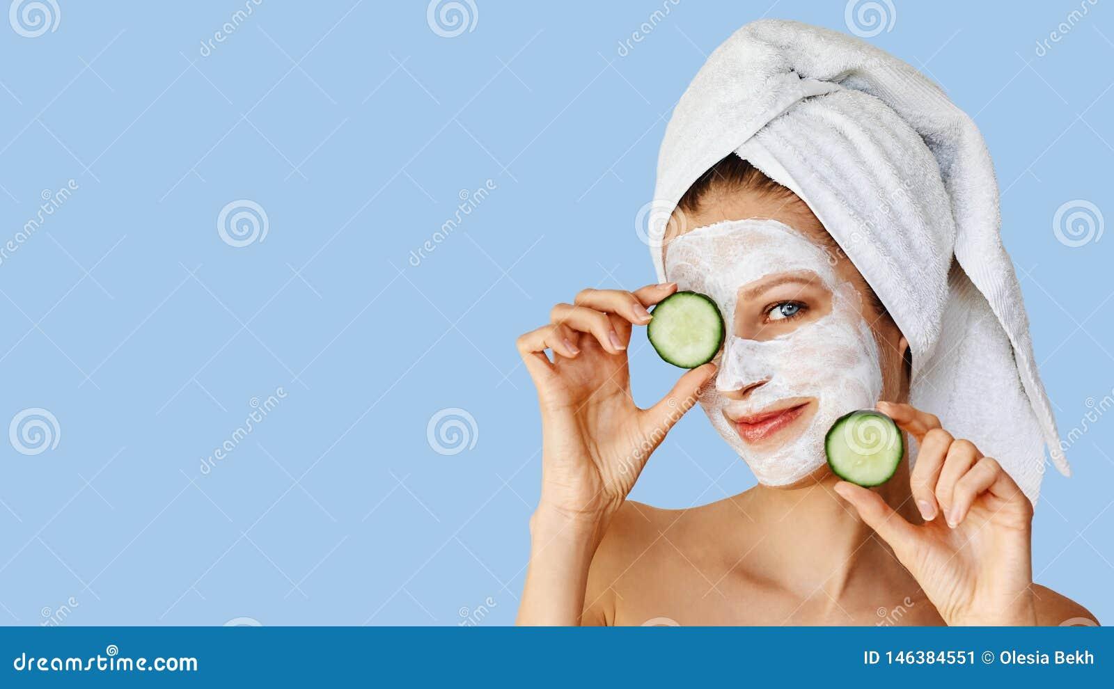 Bella giovane donna con la maschera facciale sul suo fronte che tiene le fette di cetriolo Cura di pelle e trattamento, stazione