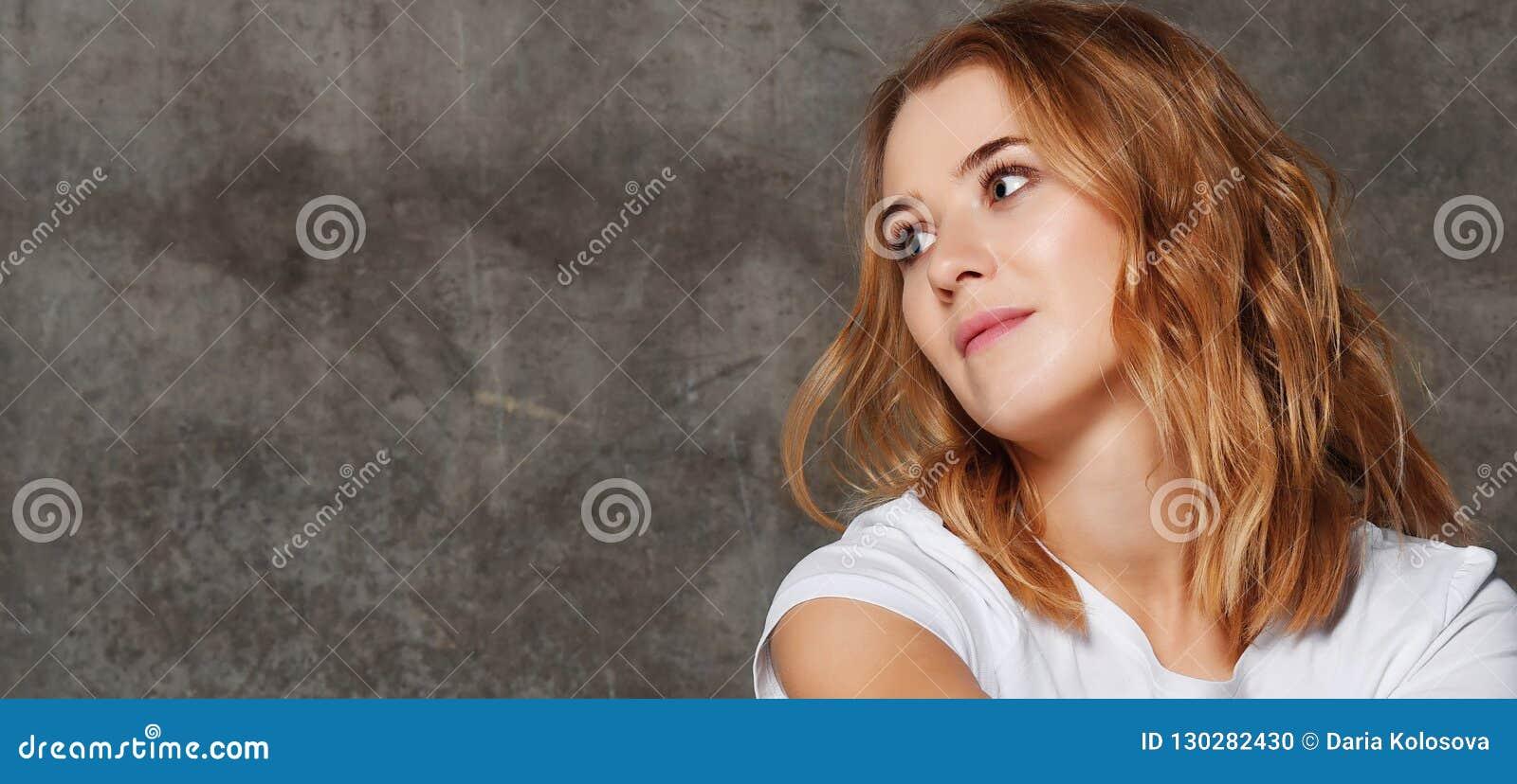 Bella giovane donna in maglietta che distoglie lo sguardo la macchina fotografica isolata contro il fondo del muro di cemento