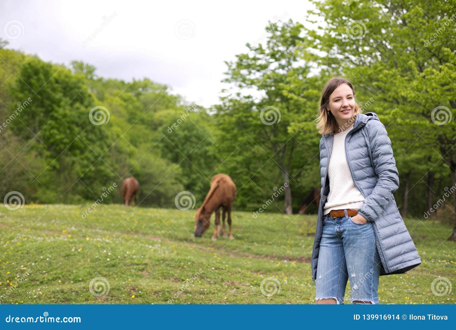 Bella giovane donna nel parco con i cavalli tempo della molla