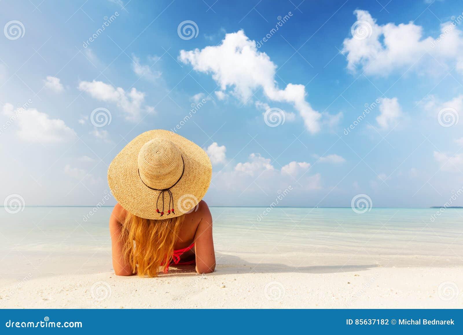 Bella giovane donna nella menzogne di cappellino da sole rilassata sulla spiaggia tropicale in Maldive
