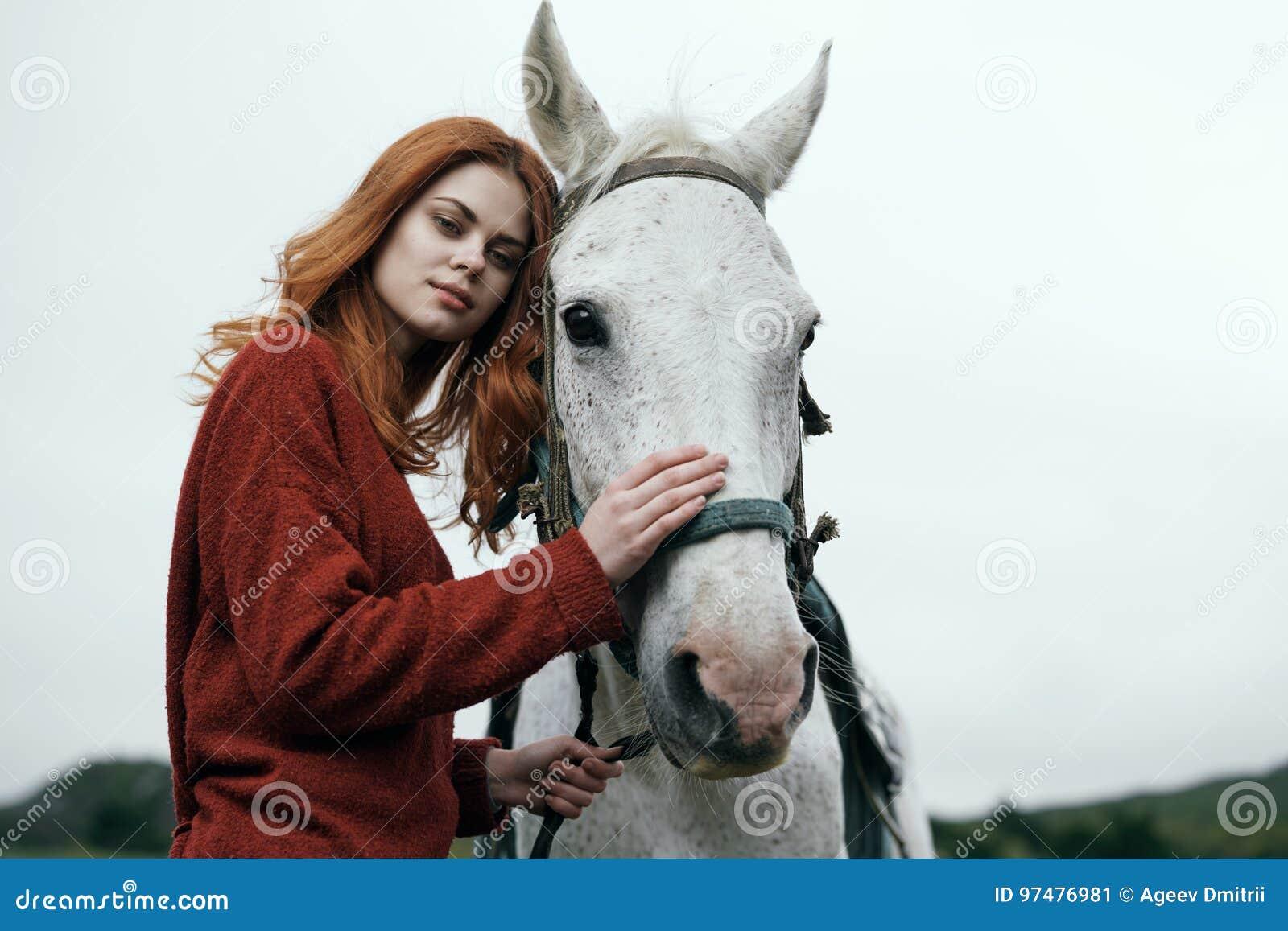 Bella giovane donna nelle montagne che tengono e che rivestono di ferro un cavallo bianco
