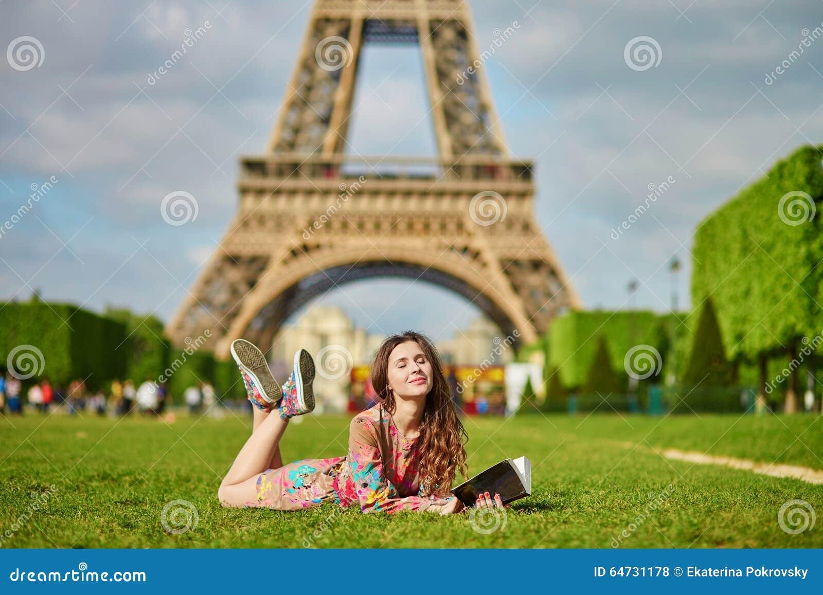 Bella giovane donna a Parigi che si trova sull erba vicino alla torre Eiffel