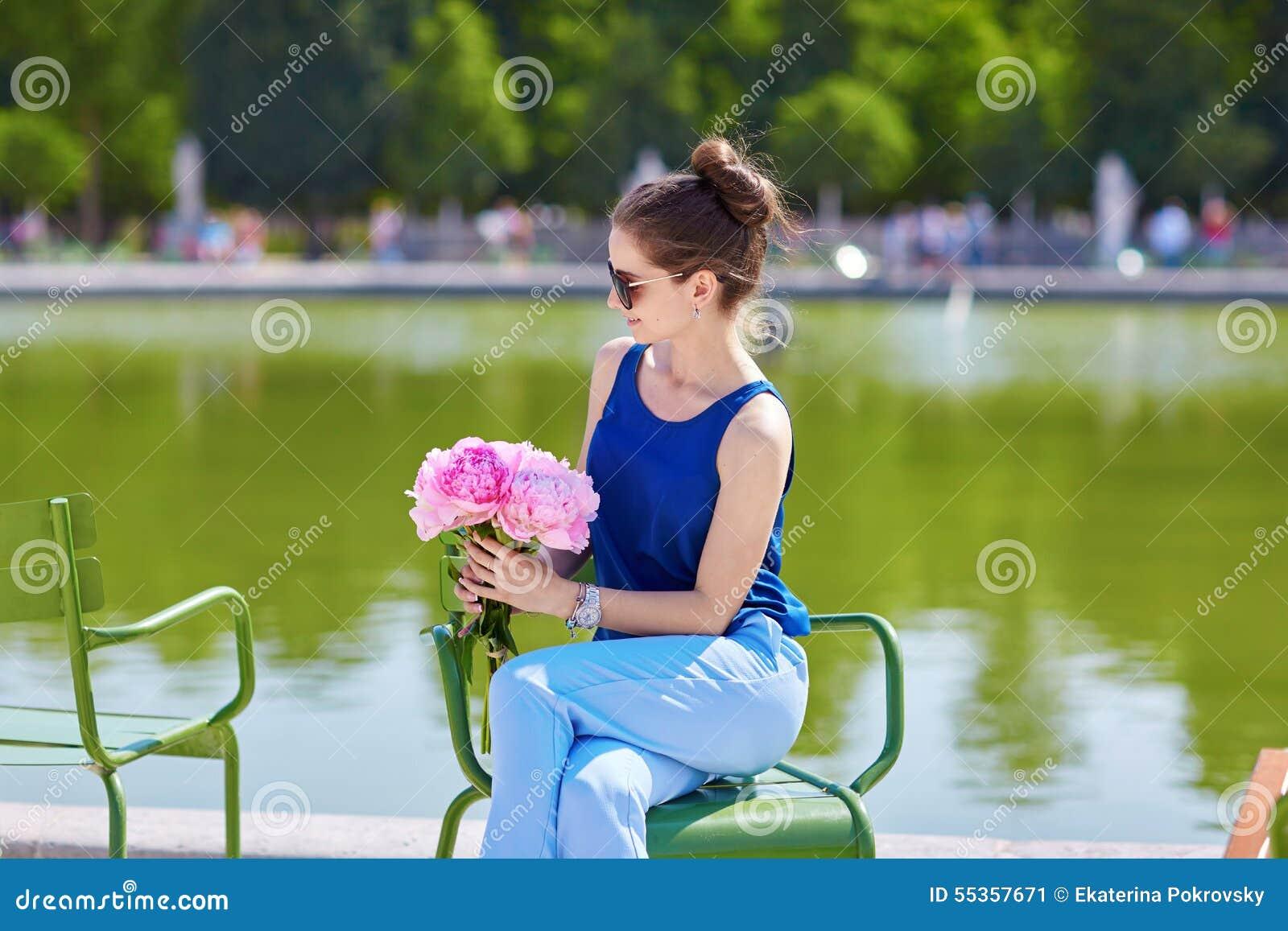 Bella giovane donna parigina con le peonie