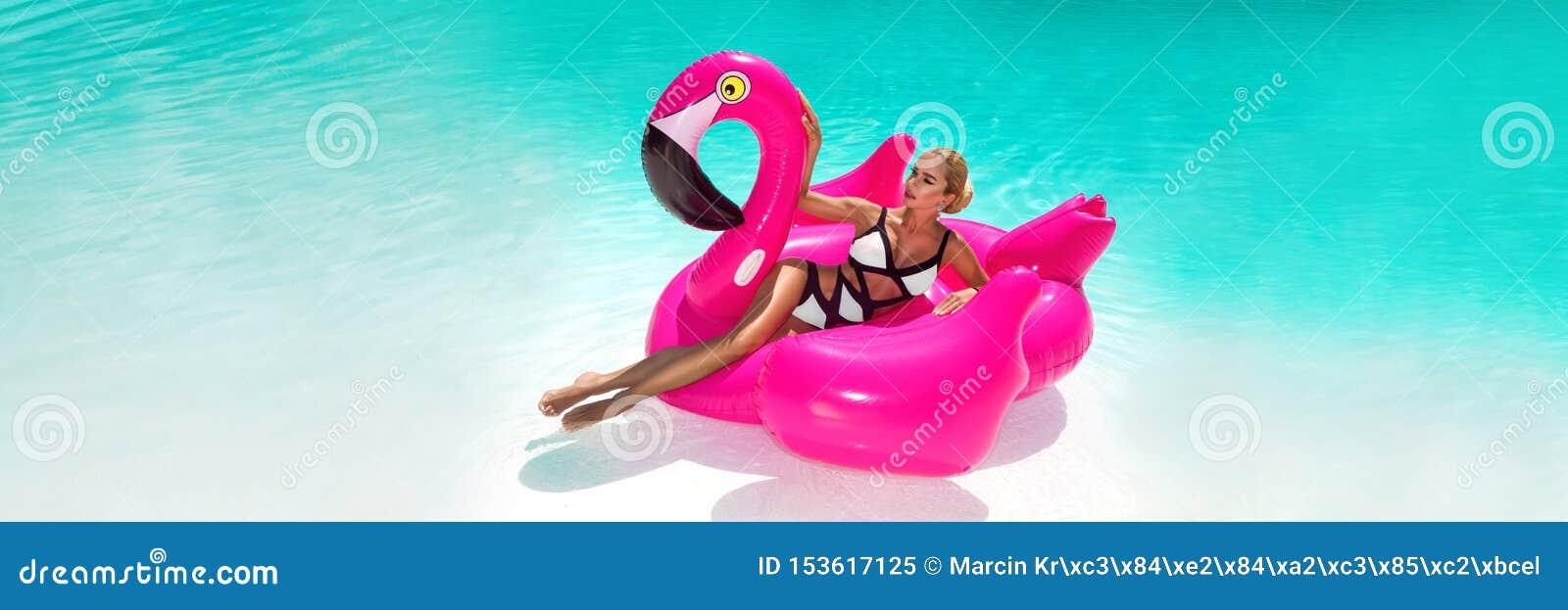 Bella giovane donna sexy e stupefacente in una piscina che si siede su un ardente rosa gonfiabile e che ride, corpo abbronzato, c