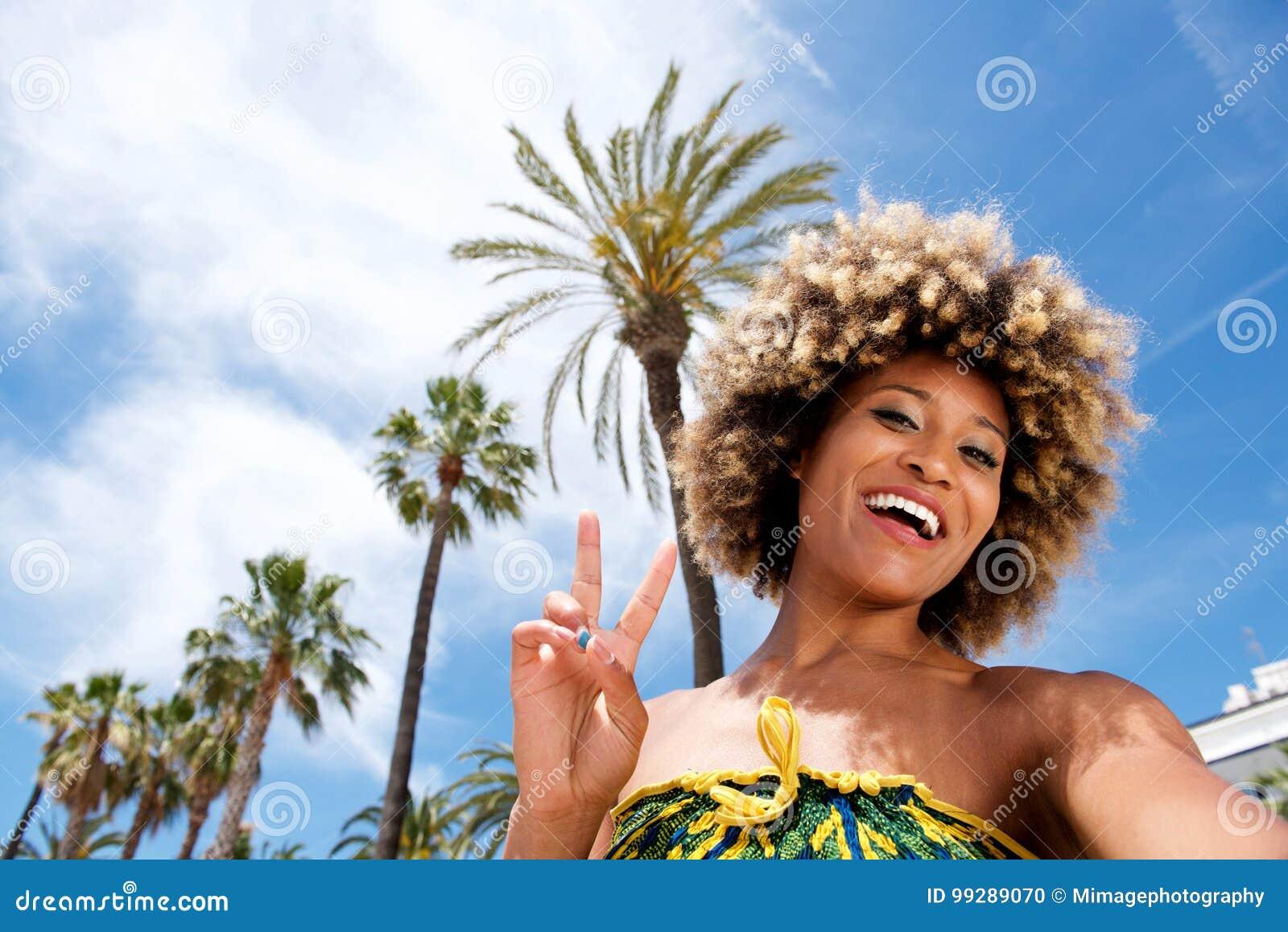 Bella giovane donna sulla vacanza alla spiaggia che prende selfie e che gesturing il segno di pace