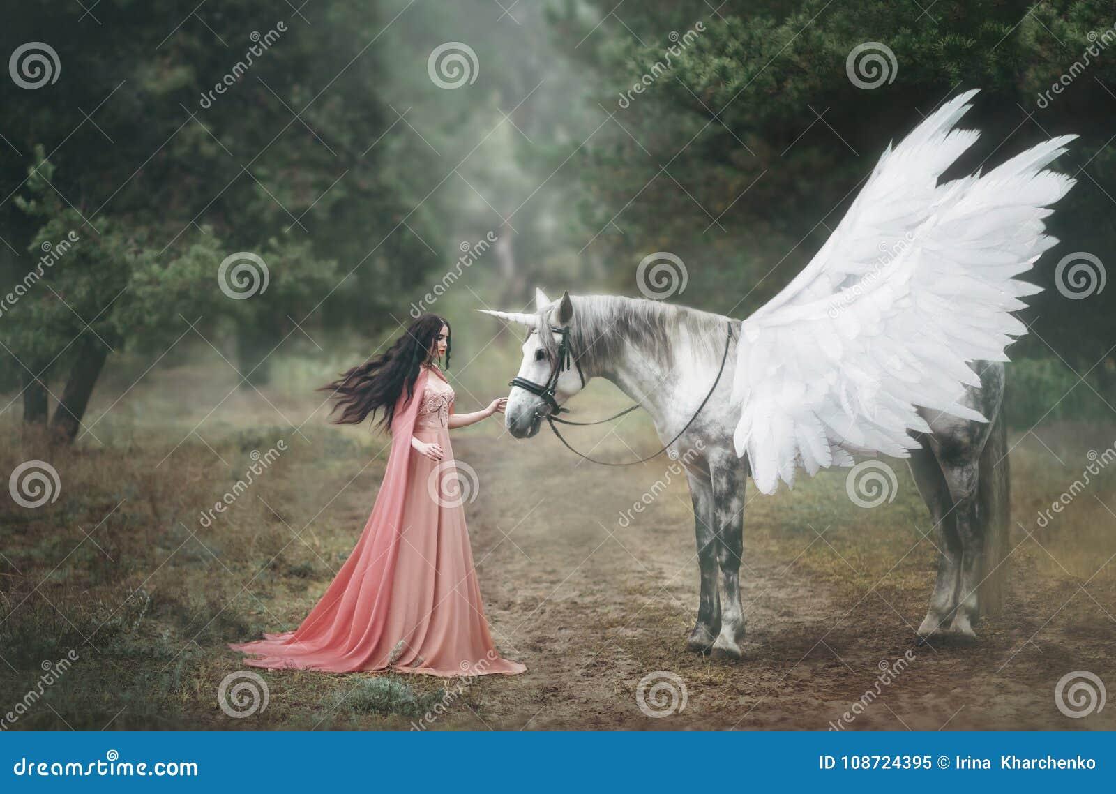 Bella, giovane elfo, camminante con un unicorno nella foresta è vestita in un vestito arancio lungo con un mantello La piuma bell