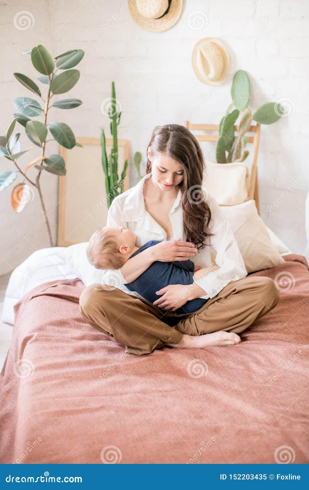 Bella giovane madre con capelli scuri lunghi nei giochi comodi familiari dei vestiti con il suo giovane figlio in una camera da l