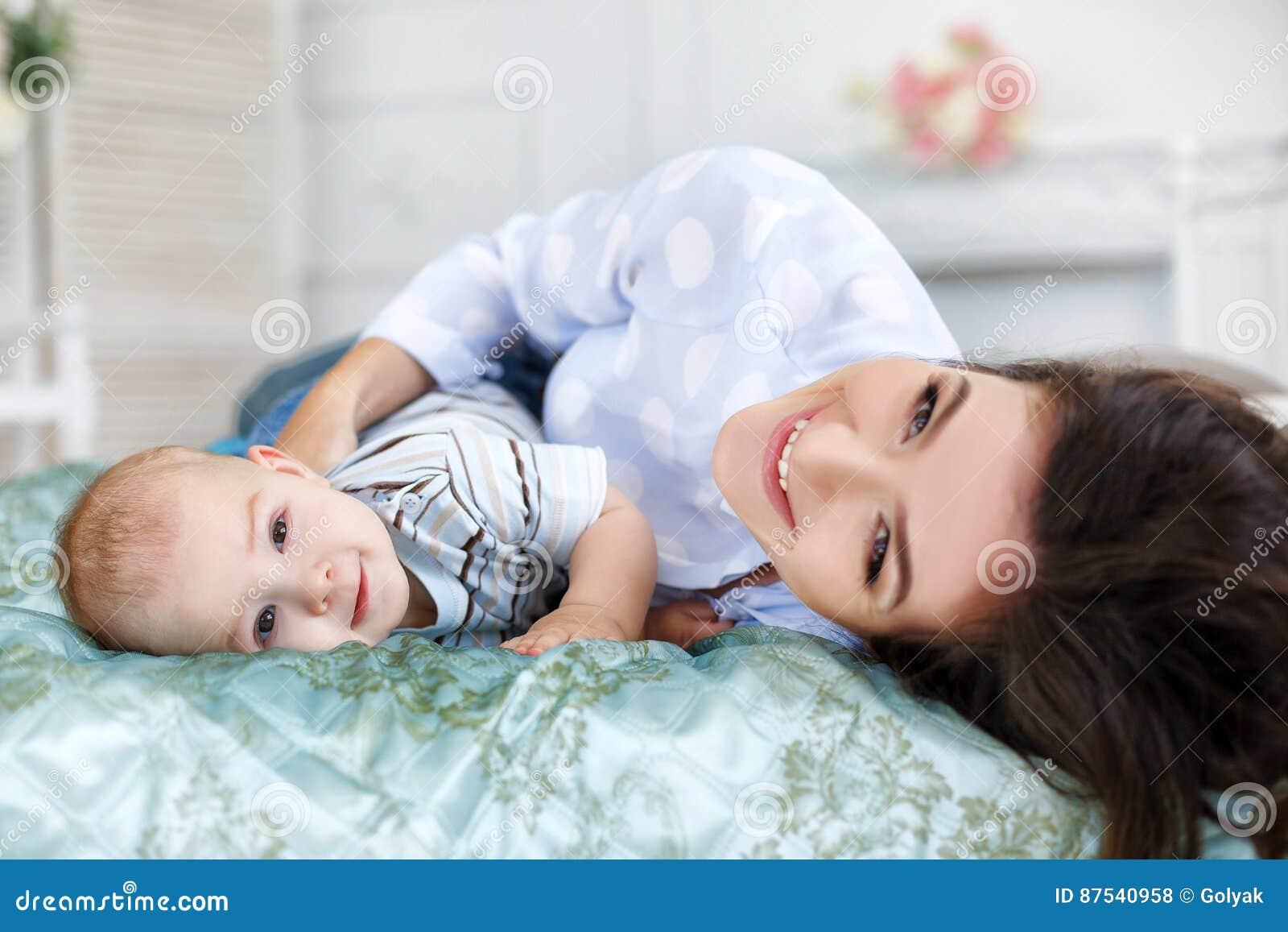 Bella giovane madre con suo figlio del neonato che si trova sul letto nella sua camera da letto - Letto che si chiude ...