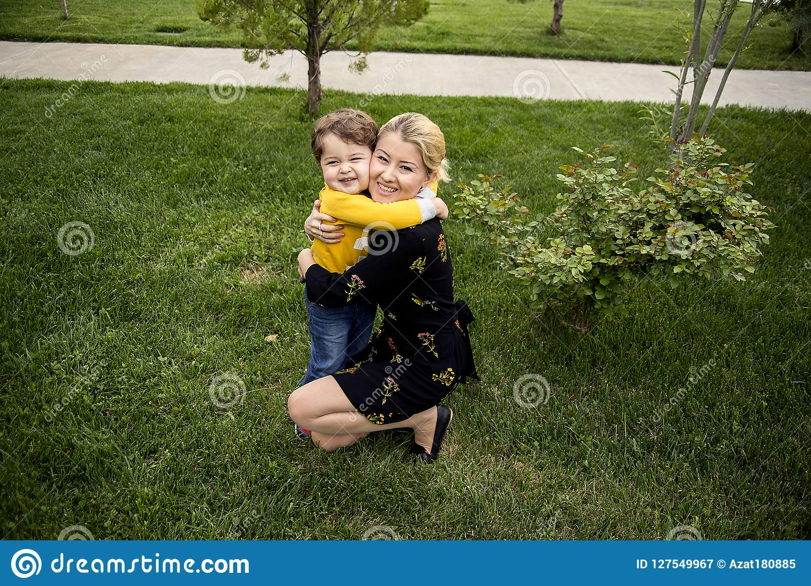 Bella giovane madre con un piccolo figlio sveglio sono felici, abbracciare, mostrante il loro amore puro