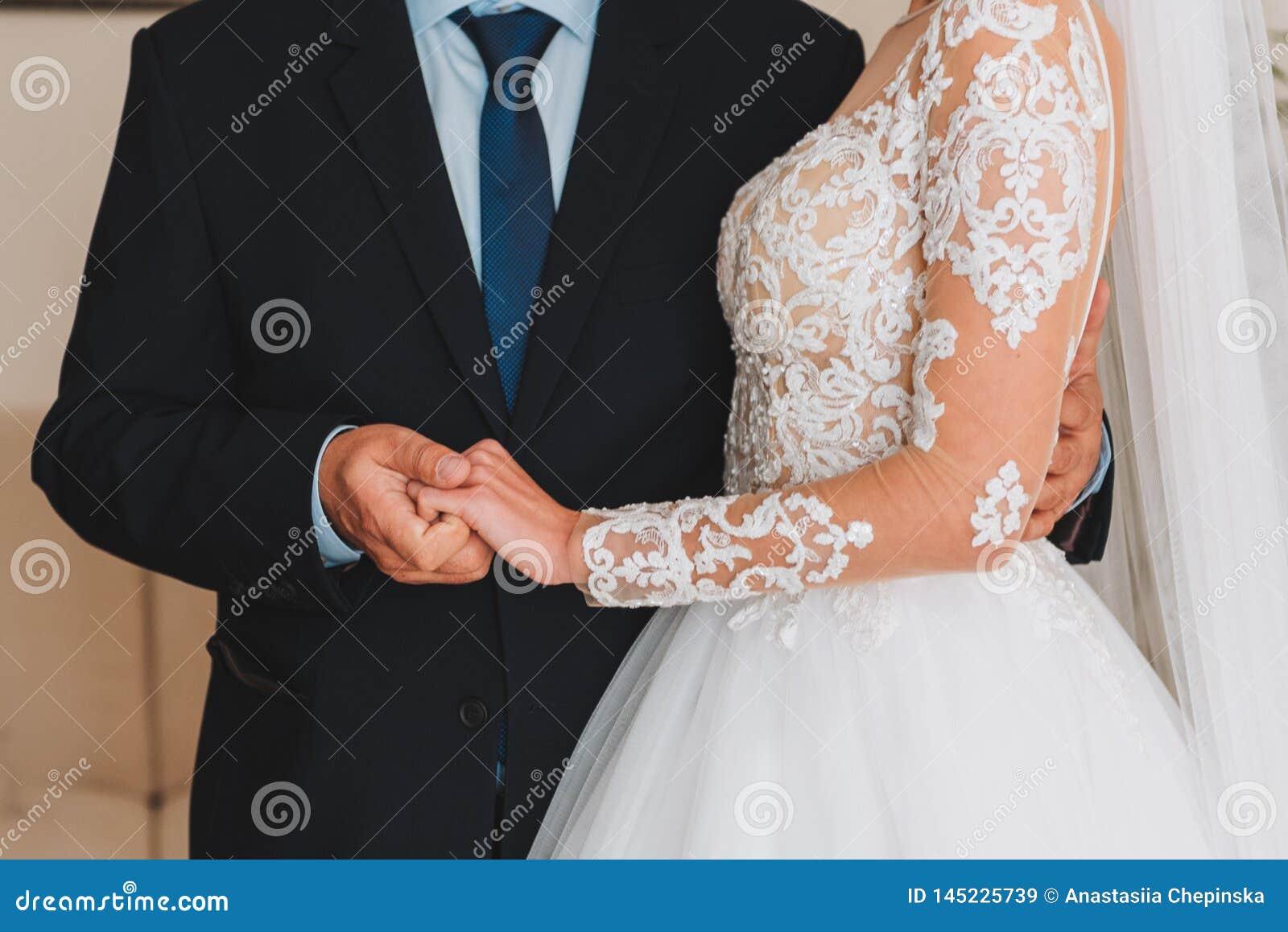 Bella giovane sposa esile che tiene la mano di suo padre prima delle sue nozze