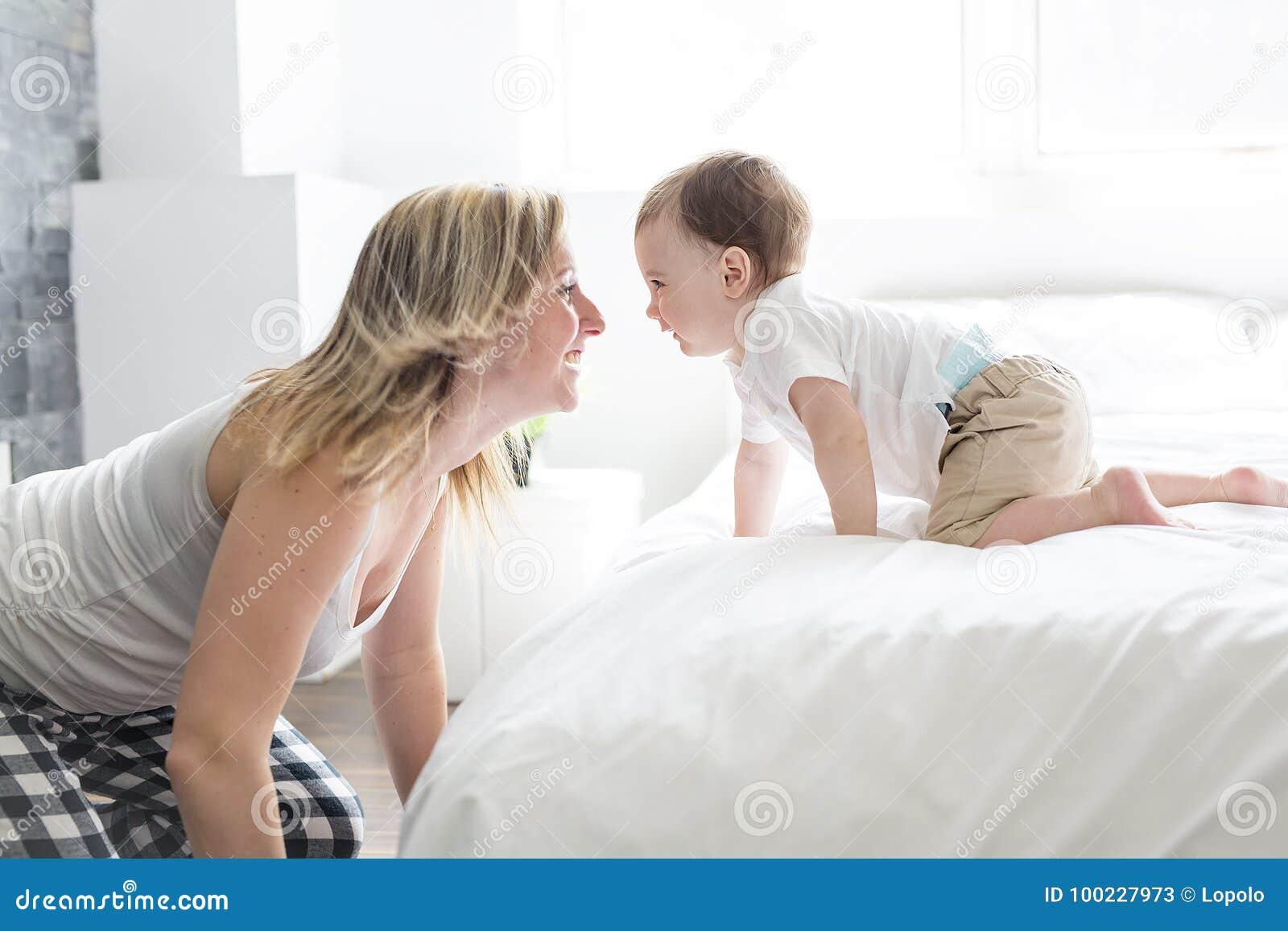 Bella giovani madre e figlio che si trovano insieme su un letto immagine stock immagine di - Letto che si chiude ...