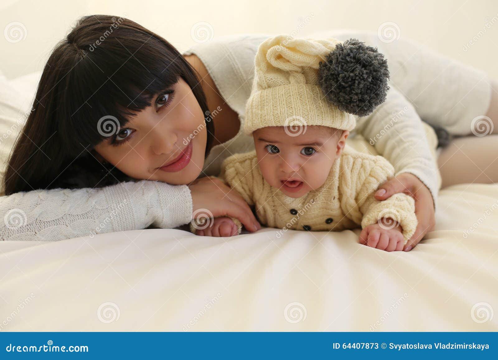 Bella madre con brevi capelli scuri ed il suo piccolo neonato sveglio