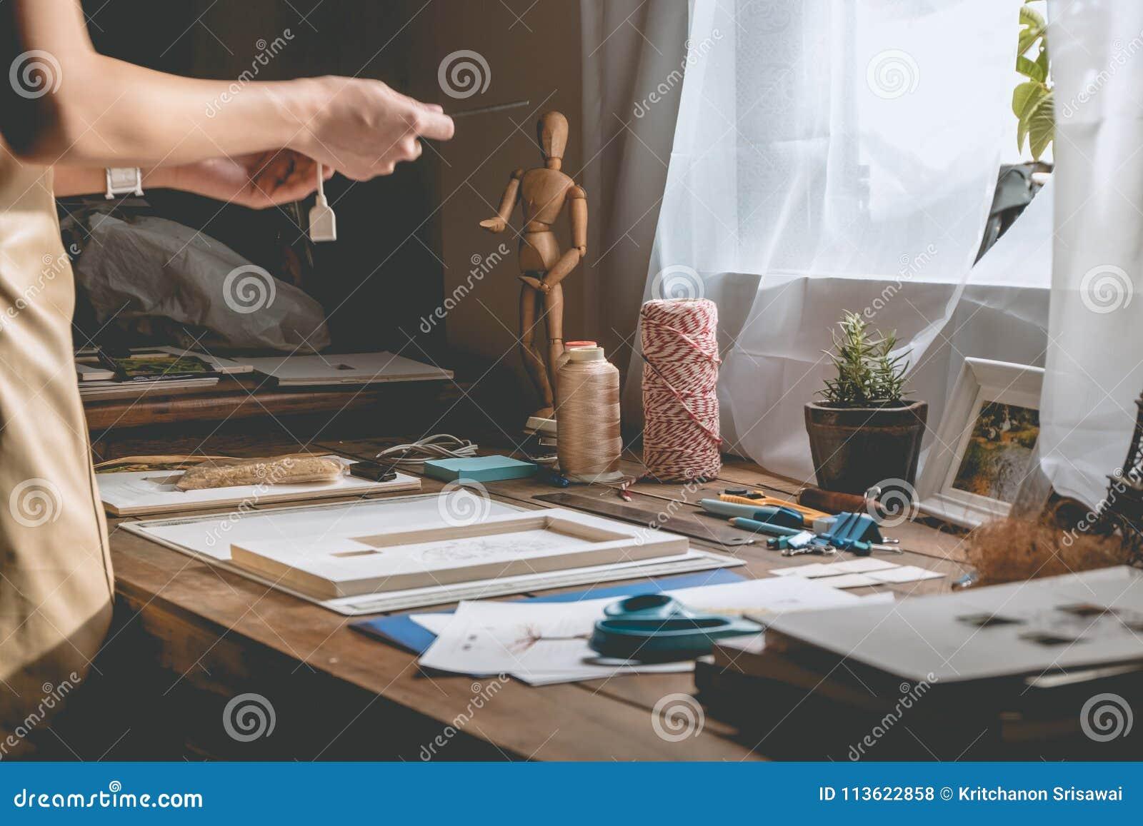 Bella mano della donna che elabora libro al ripiano del tavolo con cancelleria