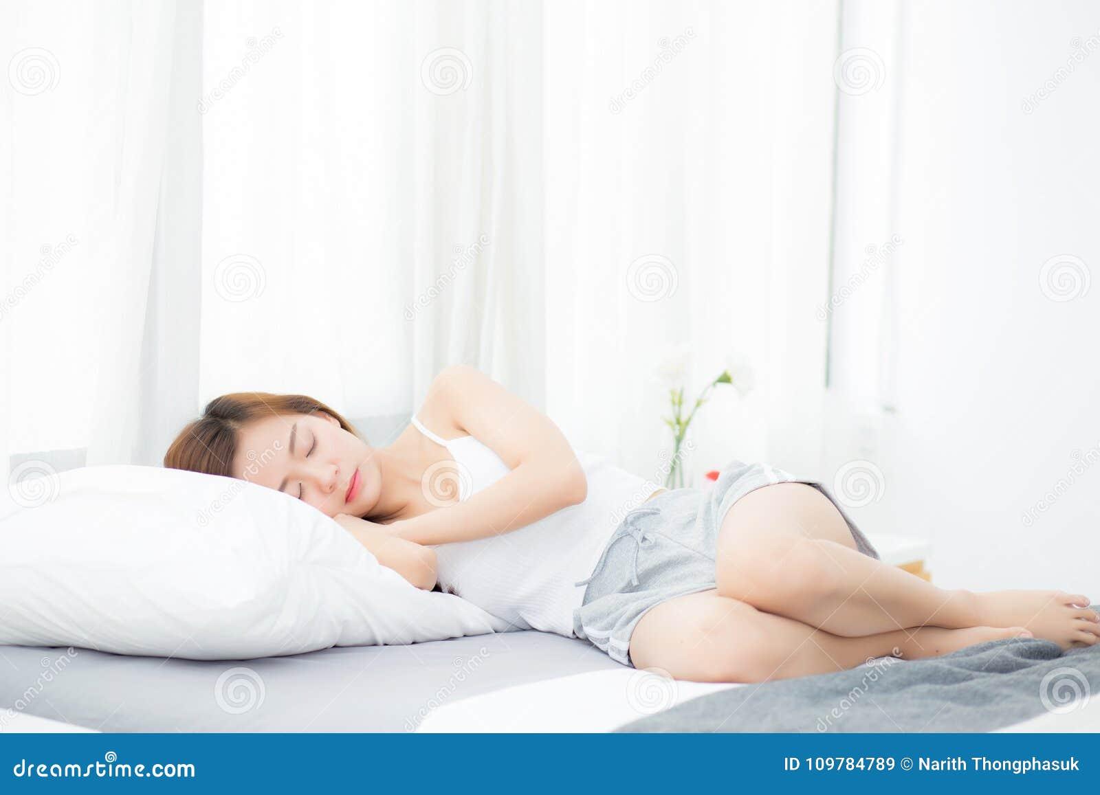 Bella menzogne asiatica di sonno della giovane donna a letto con la testa sul cuscino comodo e felice