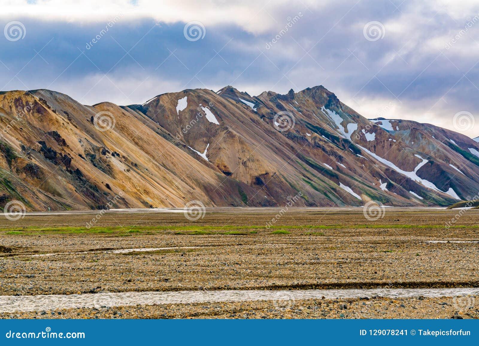 Bella montagna e la valle con la corrente dello sno di fusione