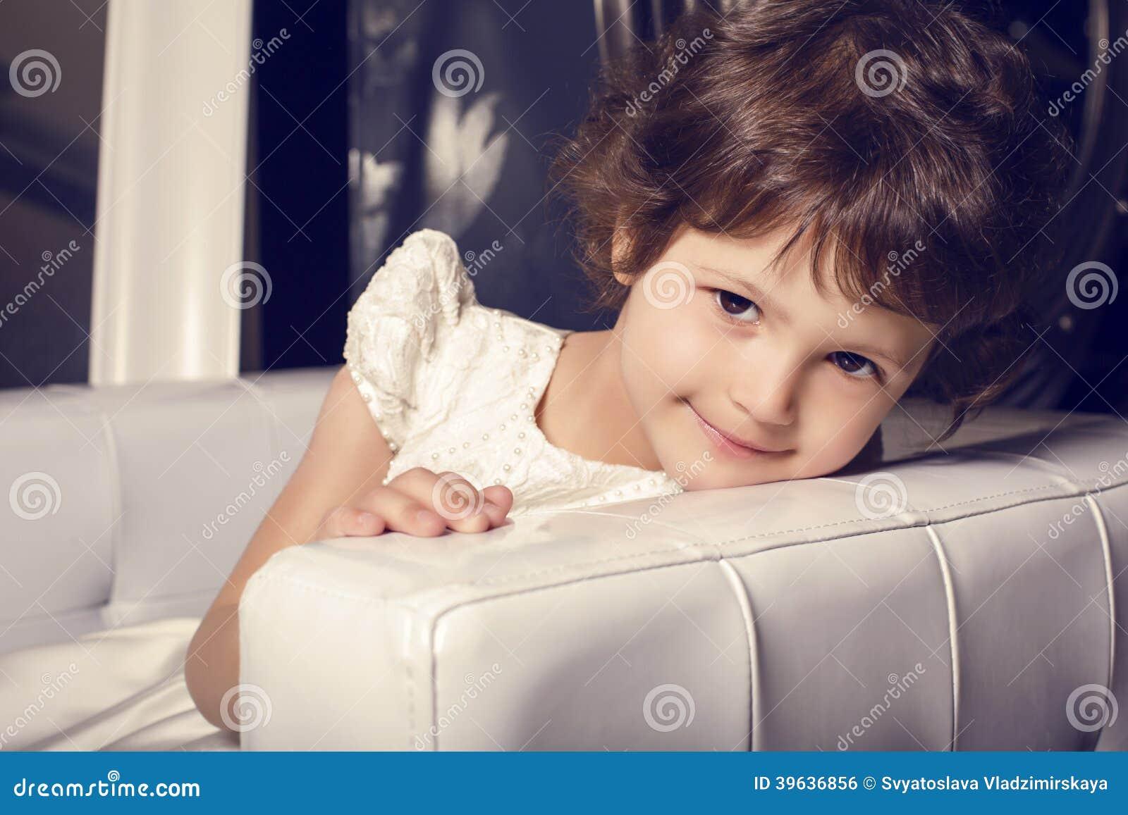 Bella piccola ragazza sveglia in vestito elegante