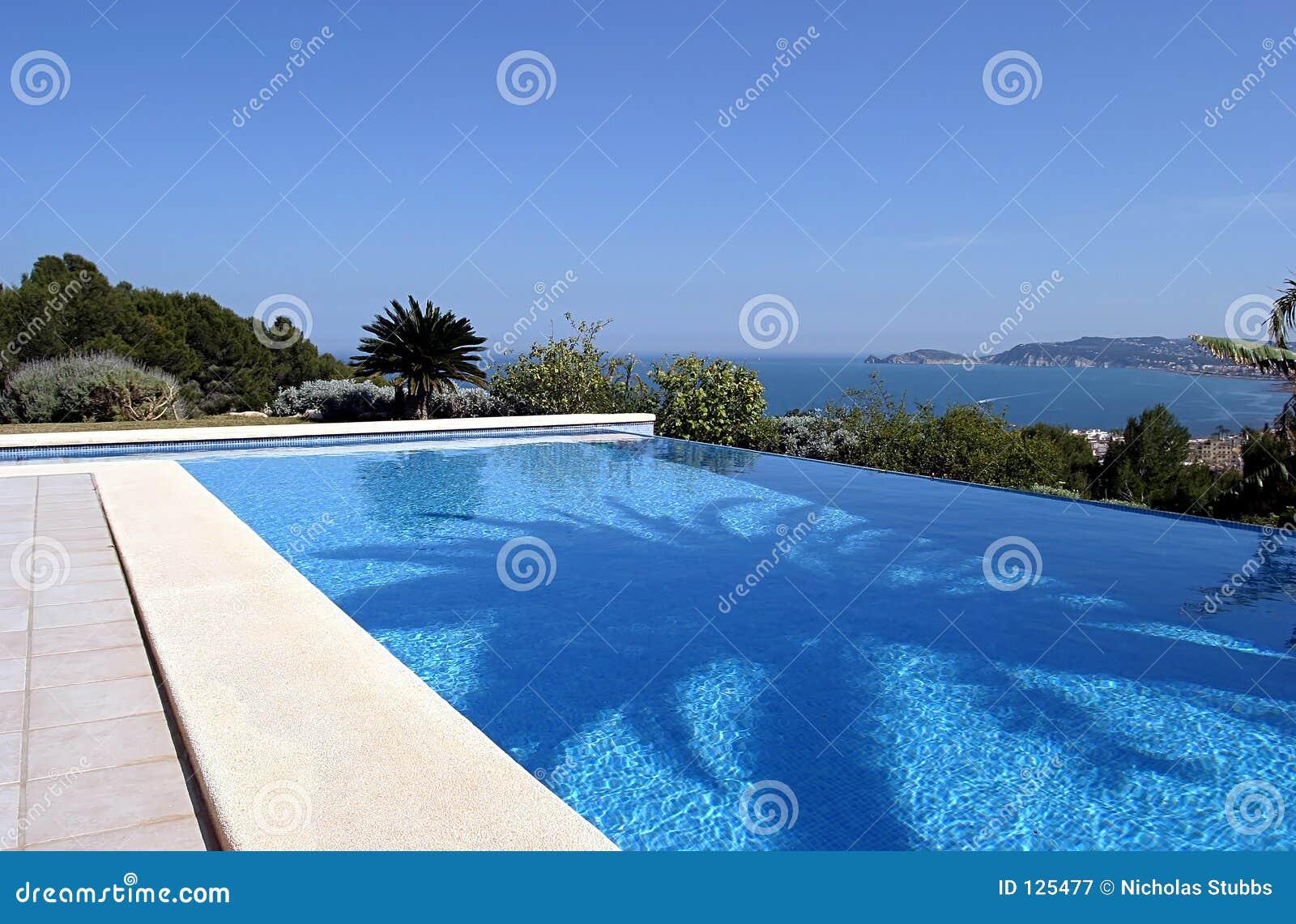 Bella piscina fresca blu di infinità in una villa in Spagna piena di sole con le viste del mare