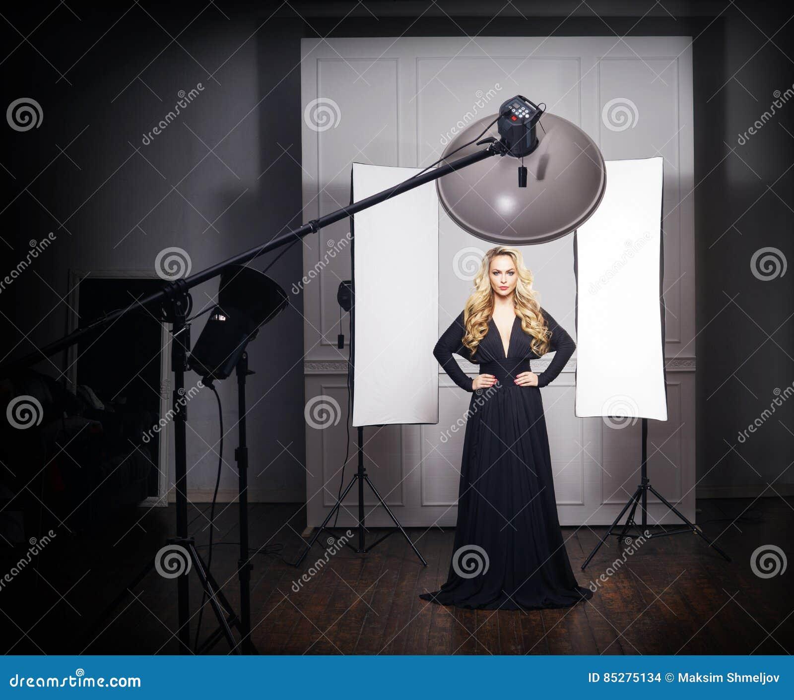 Bella posa di modello in vestito nero nello studio della foto
