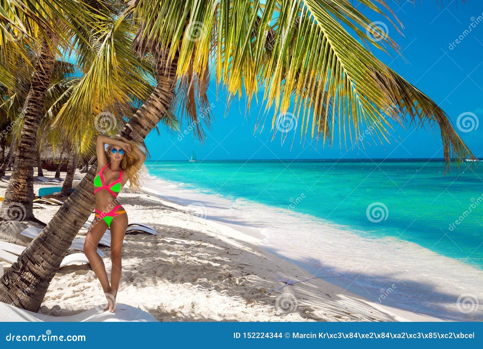 Bella ragazza abbronzata nei supporti alla moda del bikini accanto ad una palma sulla spiaggia di un isola tropicale Vacanze esti