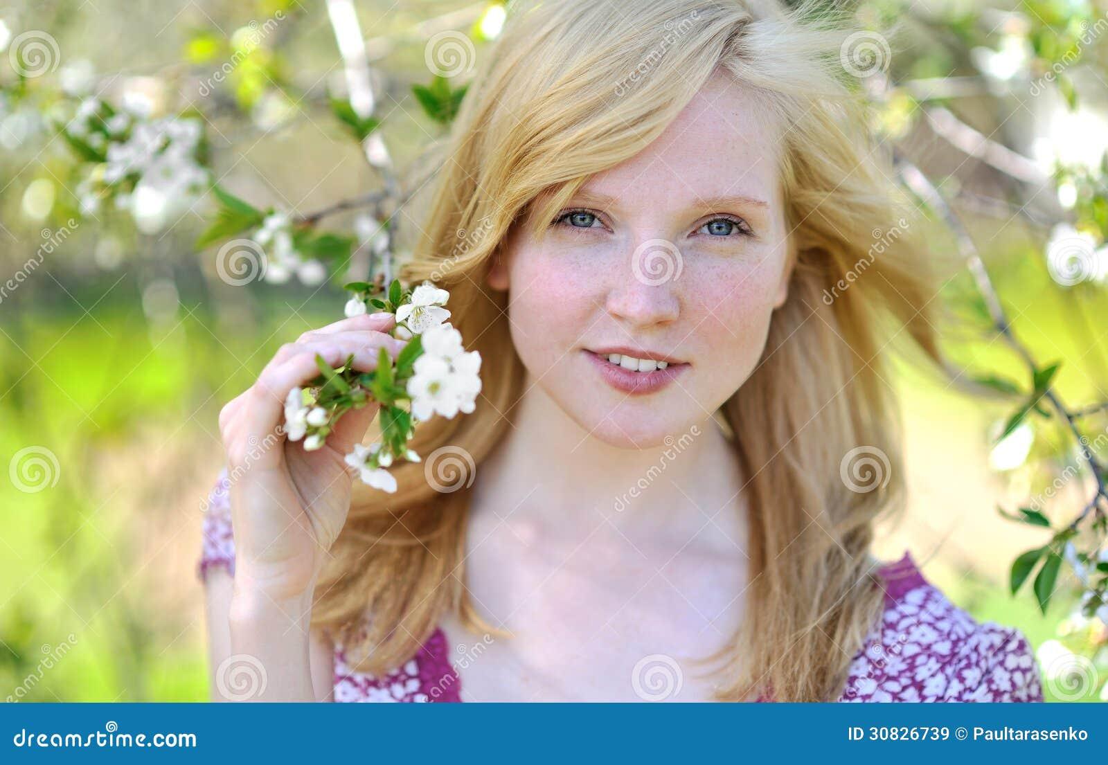 Bella ragazza in albero di fioritura - ritratto soleggiato della molla
