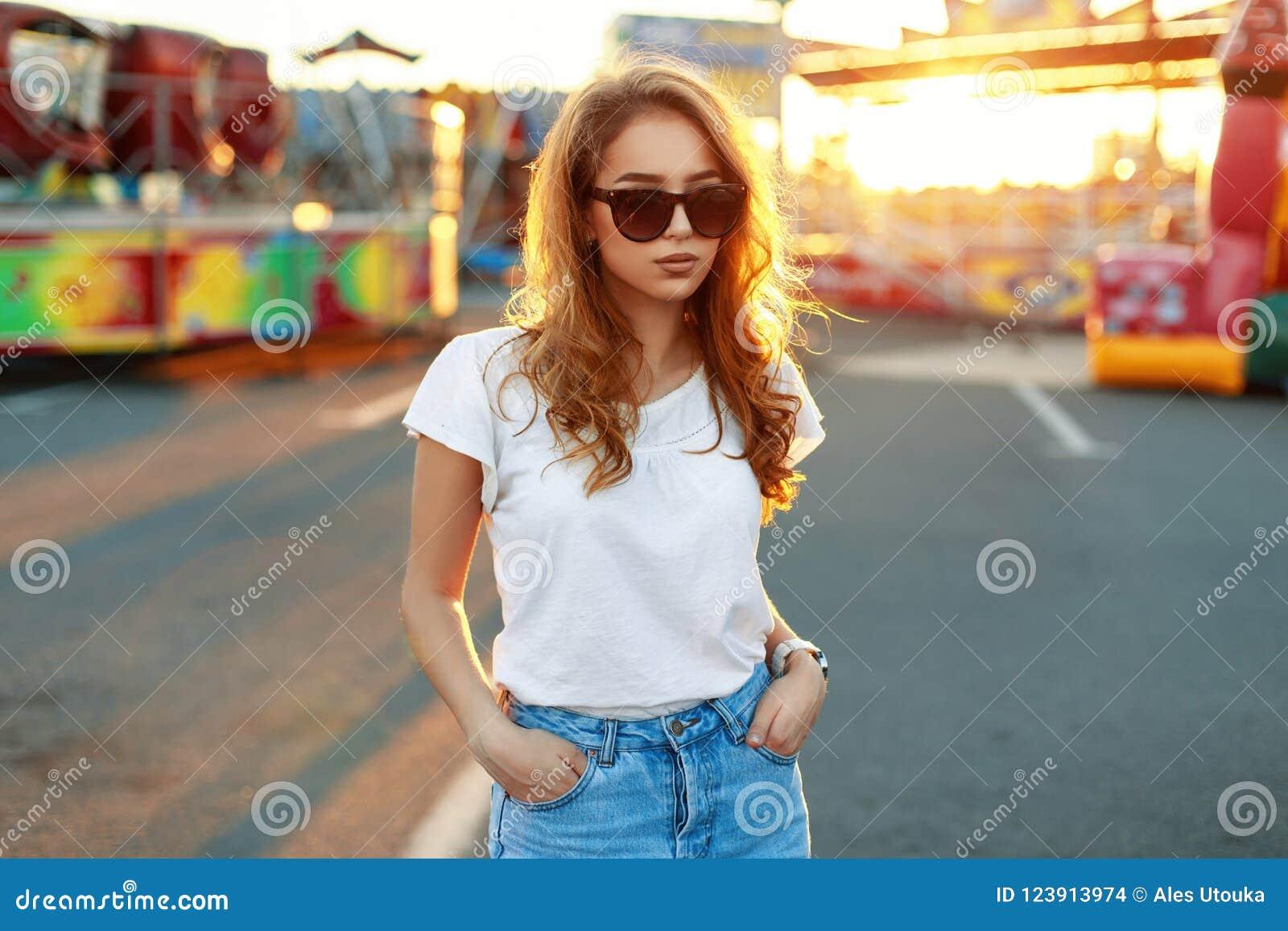 Bella ragazza alla moda in occhiali da sole al fondo di tramonto