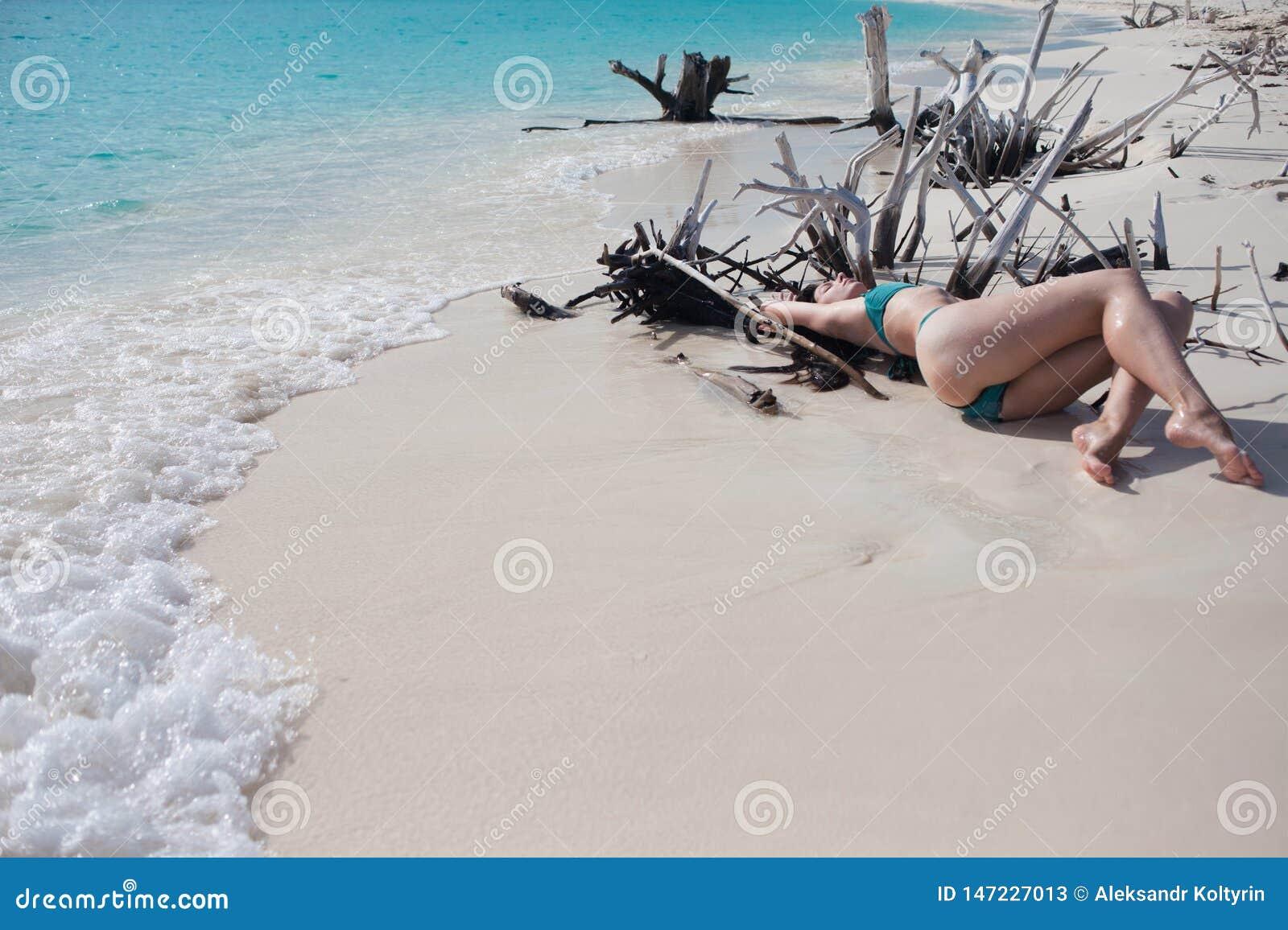 Bella ragazza in bikini che si trova fra le spine di legno sulla spiaggia